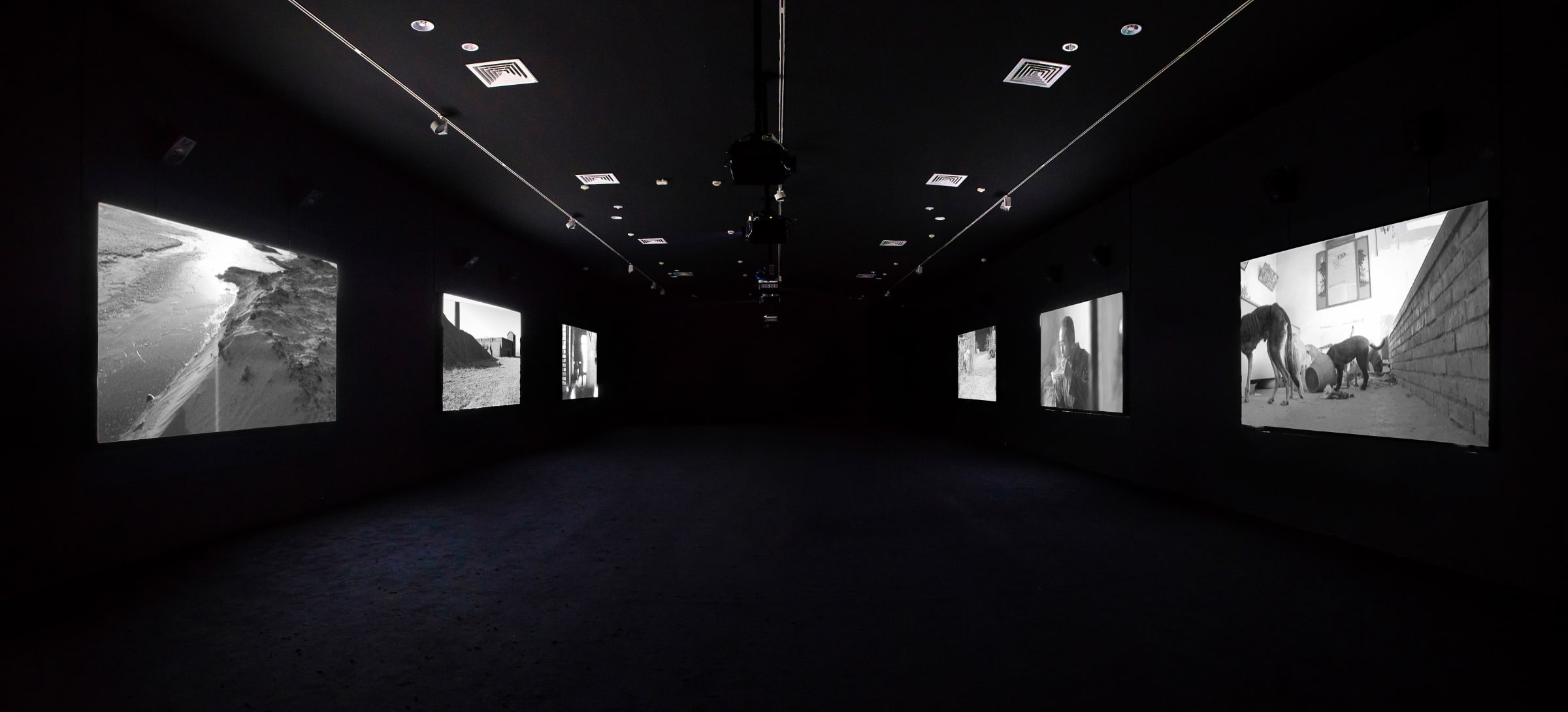 Six black and white images are projected on both sides of a dark room.