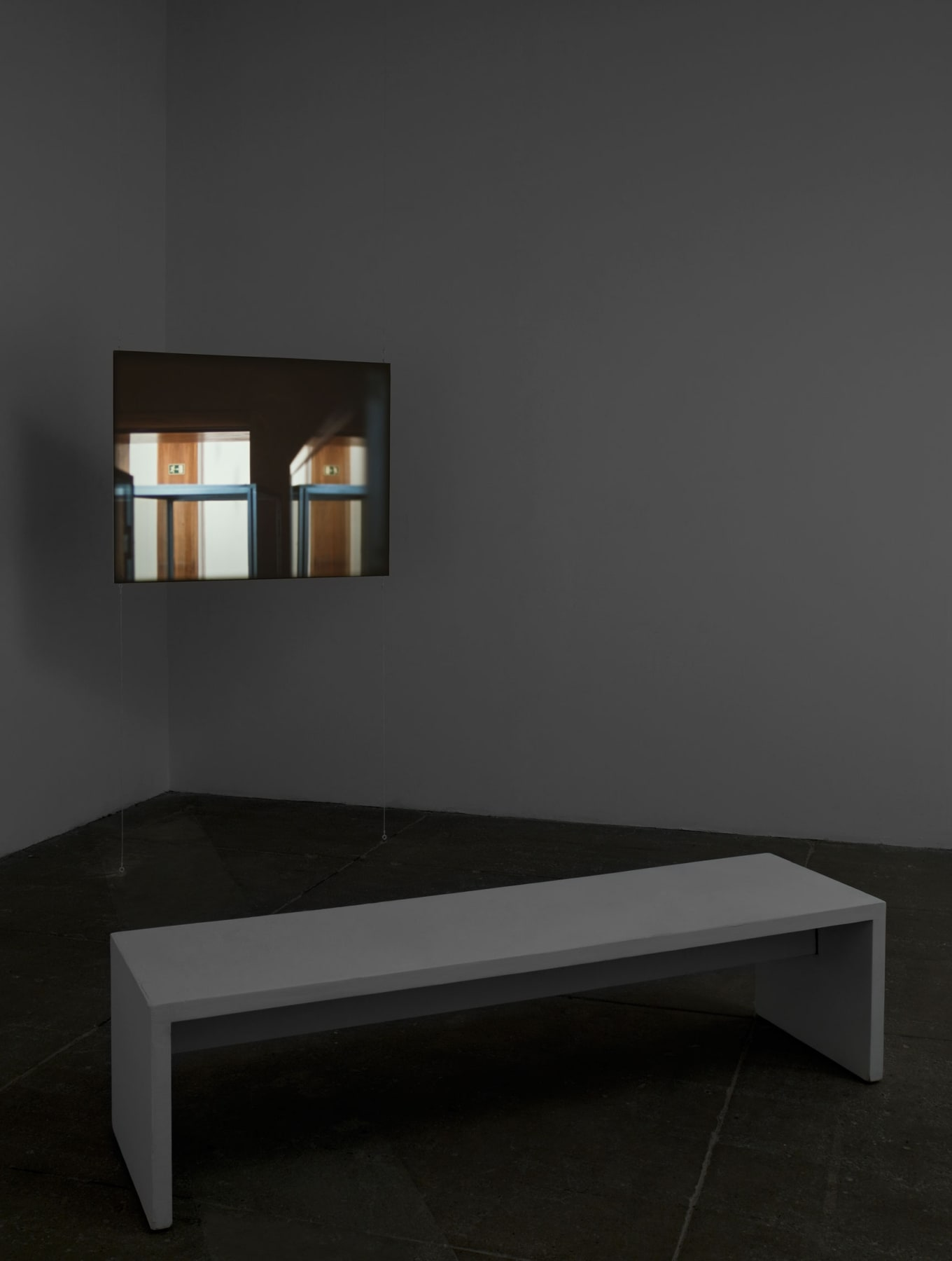 A white bench sits in front of a small screen displaying two doors illuminated by rays of light.