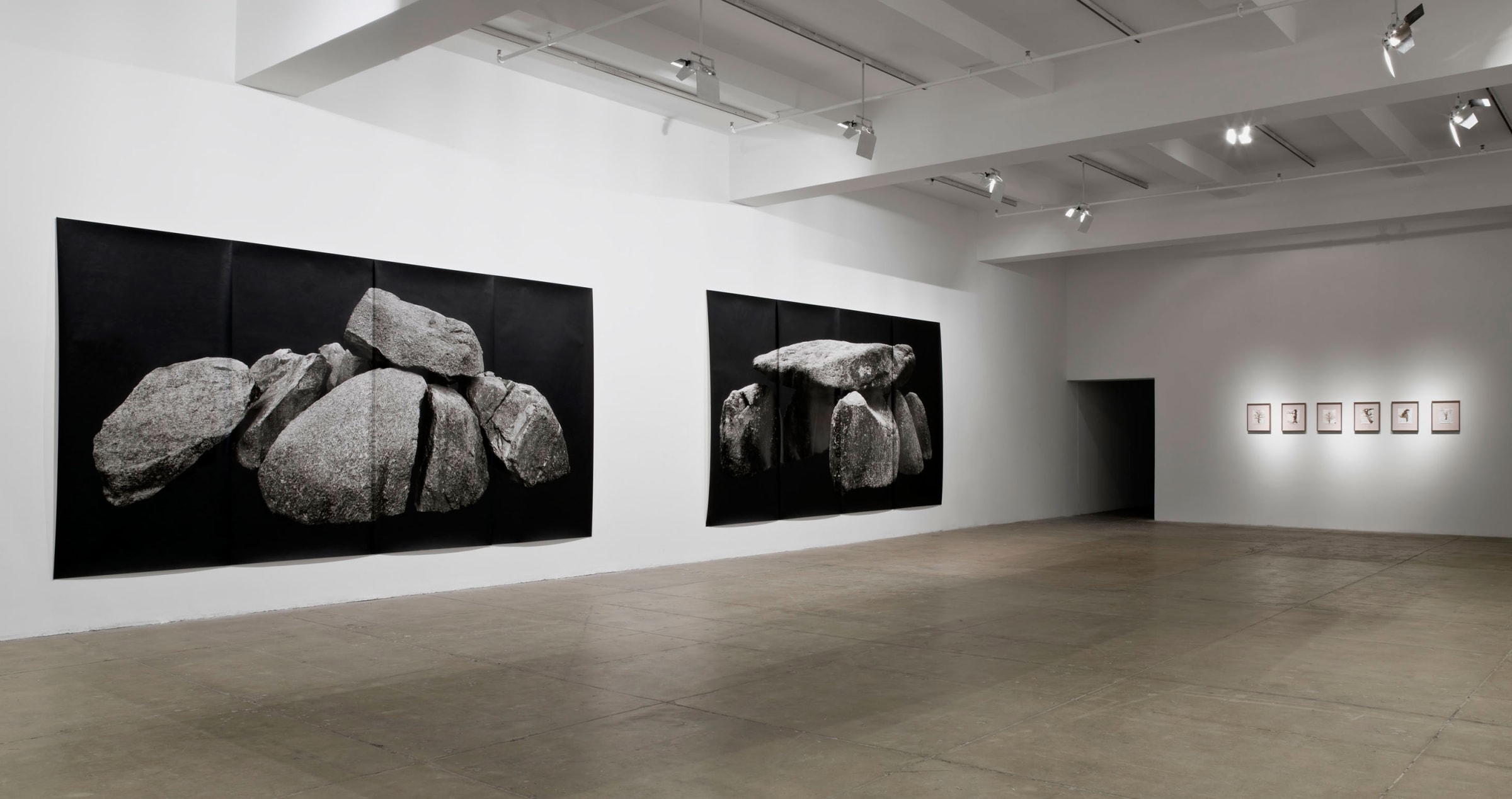 Two large prints of stacked rocks on a black background are pinned to the left wall. Six framed drawings of bare trees hang on the right wall.