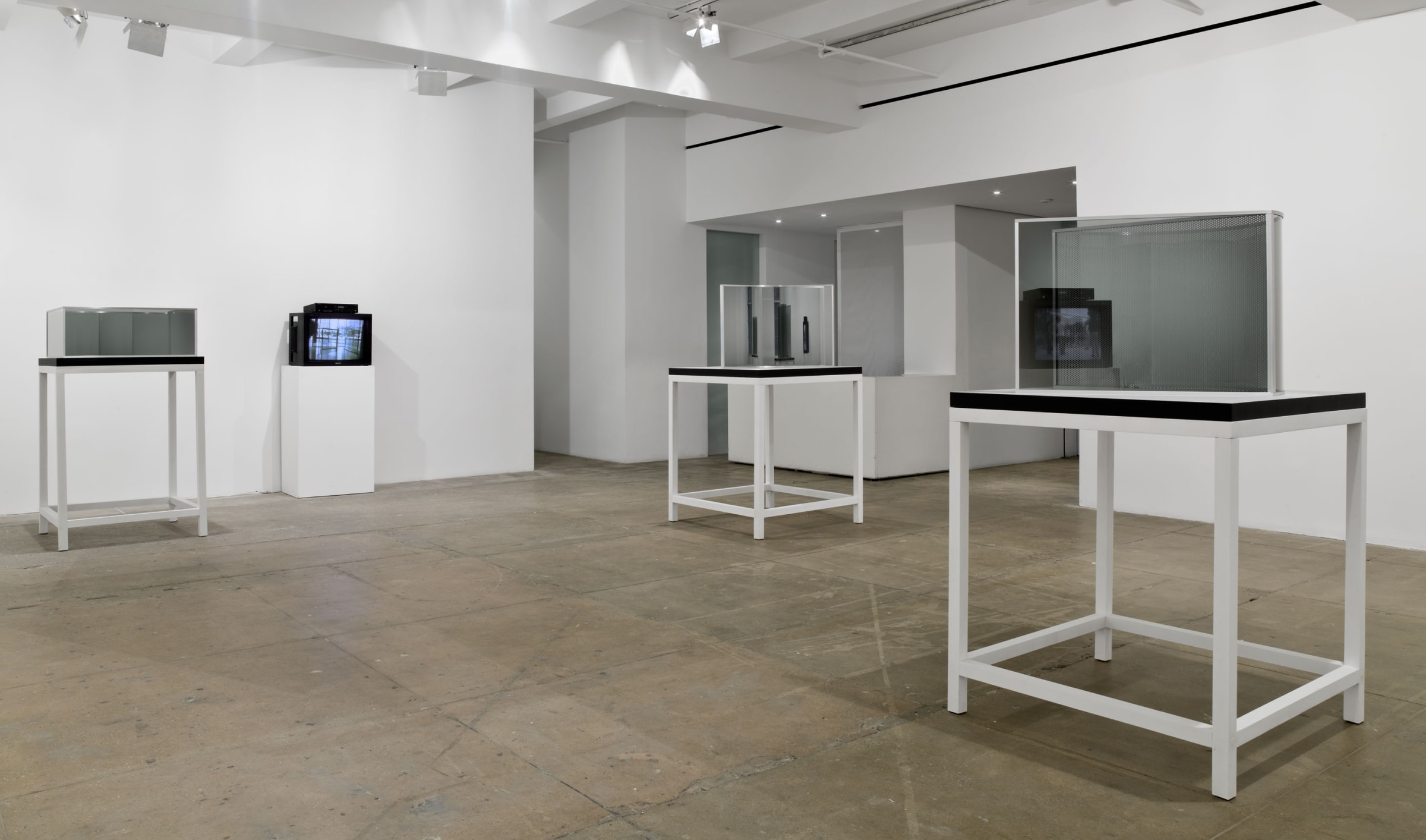 Three glass and mirror sculptures of different shapes are installed atop tables; a tv stands between projecting images.