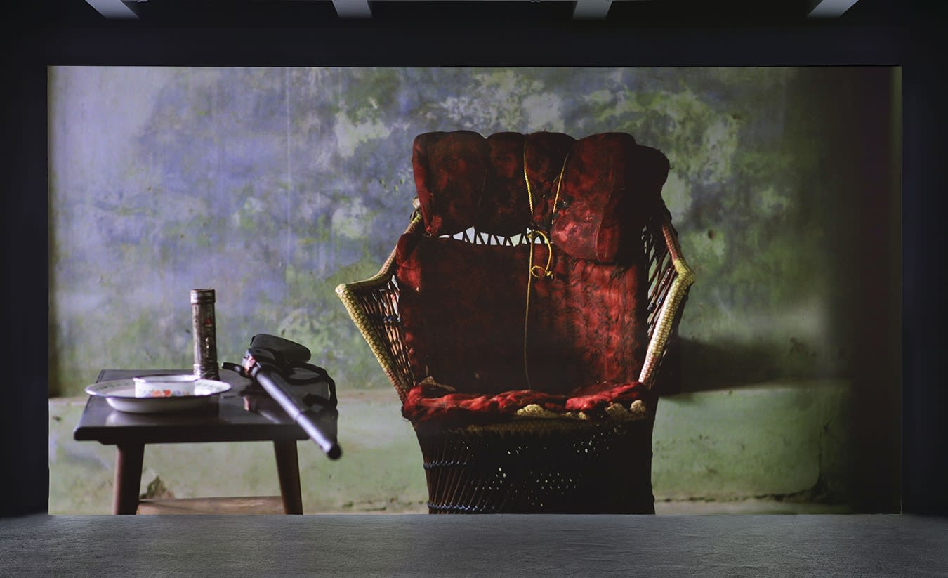 A large projection depicts a wicker chair with a red cushion, a side-table with a rifle, two plates and a metallic bottle on top.
