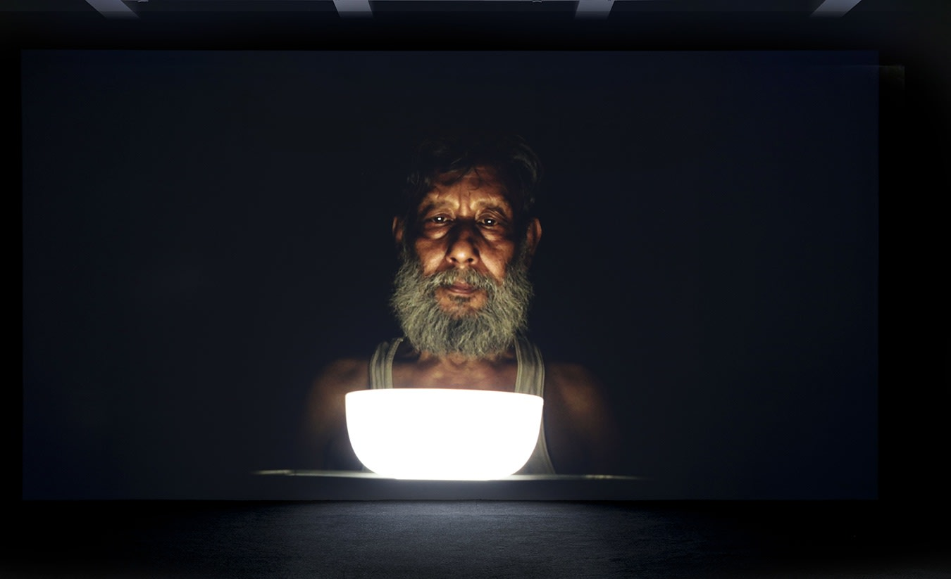 A large projection depicts an elderly brown man wearing a white tank top holding an illuminated bowl.