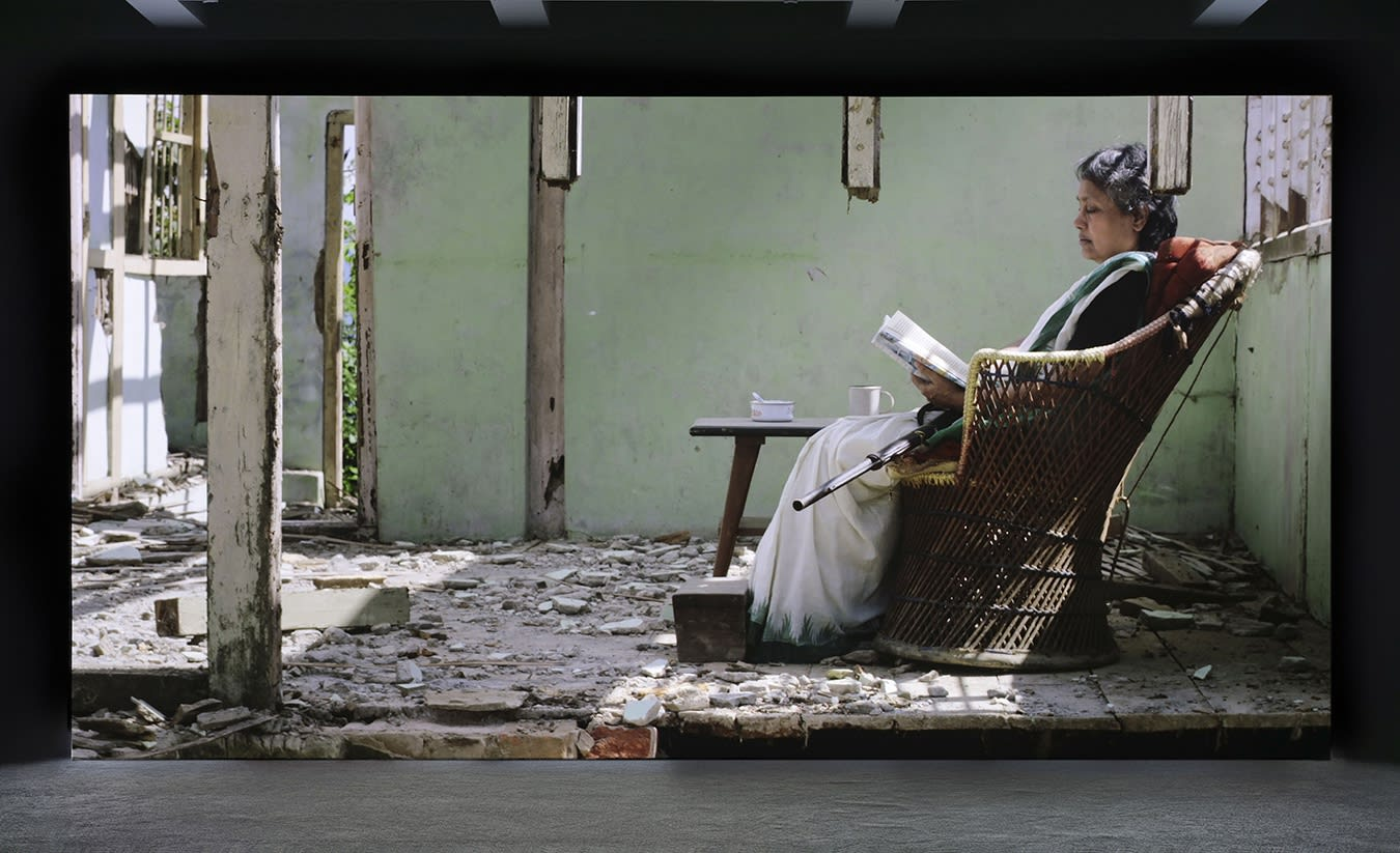 A large projection depicts an elderly woman sitting on a cushioned wicker chair in a destroyed room. A rifle sits on her lap as she reads, a teacup and ashtray are on the side-table next to her.