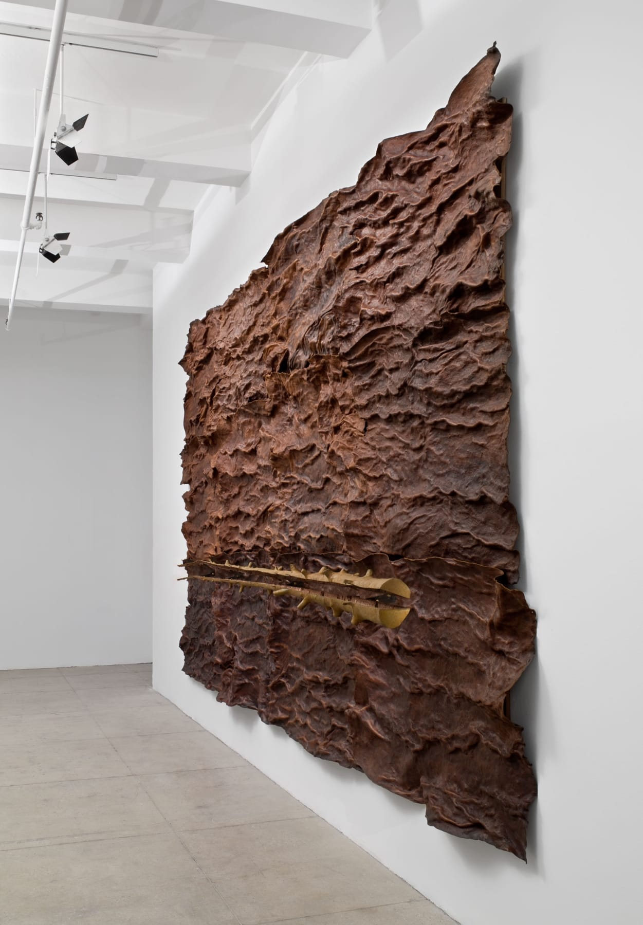 A large bark-like sculpture with a tree trunk running horizontally in front of it hangs on a white wall.
