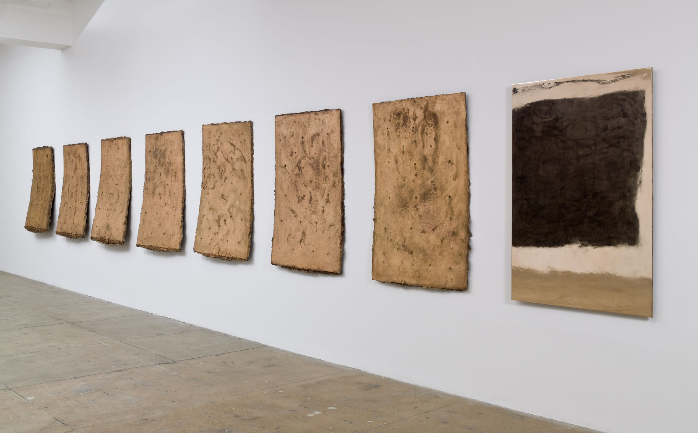 Seven cut outs of what appears to be beige leather hang on a white wall. The right most piece is painted black and white, the rest are bare.