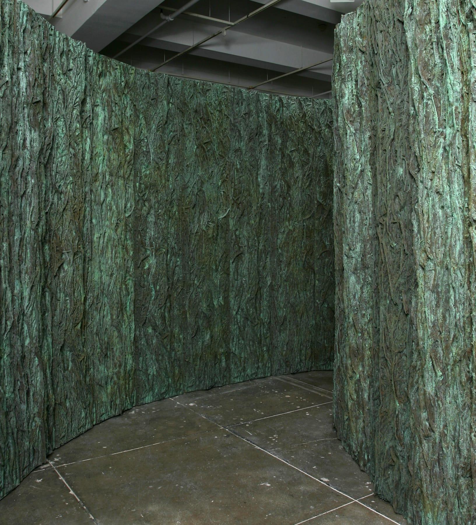A winding corridor of jade green, bark like walls on a beige floor.