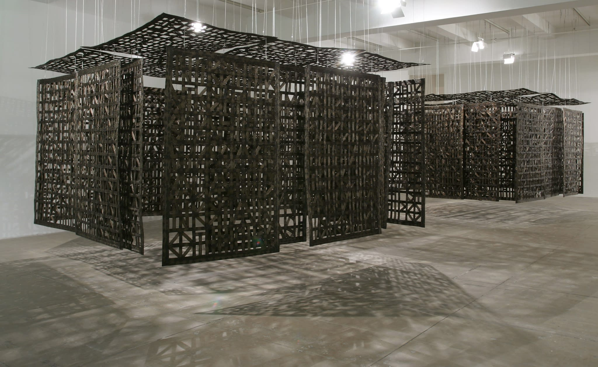 A large wooden sculpture, made up of several panels made up of wooden carved patterns which hang from the ceiling, forming a partially enclosed space.