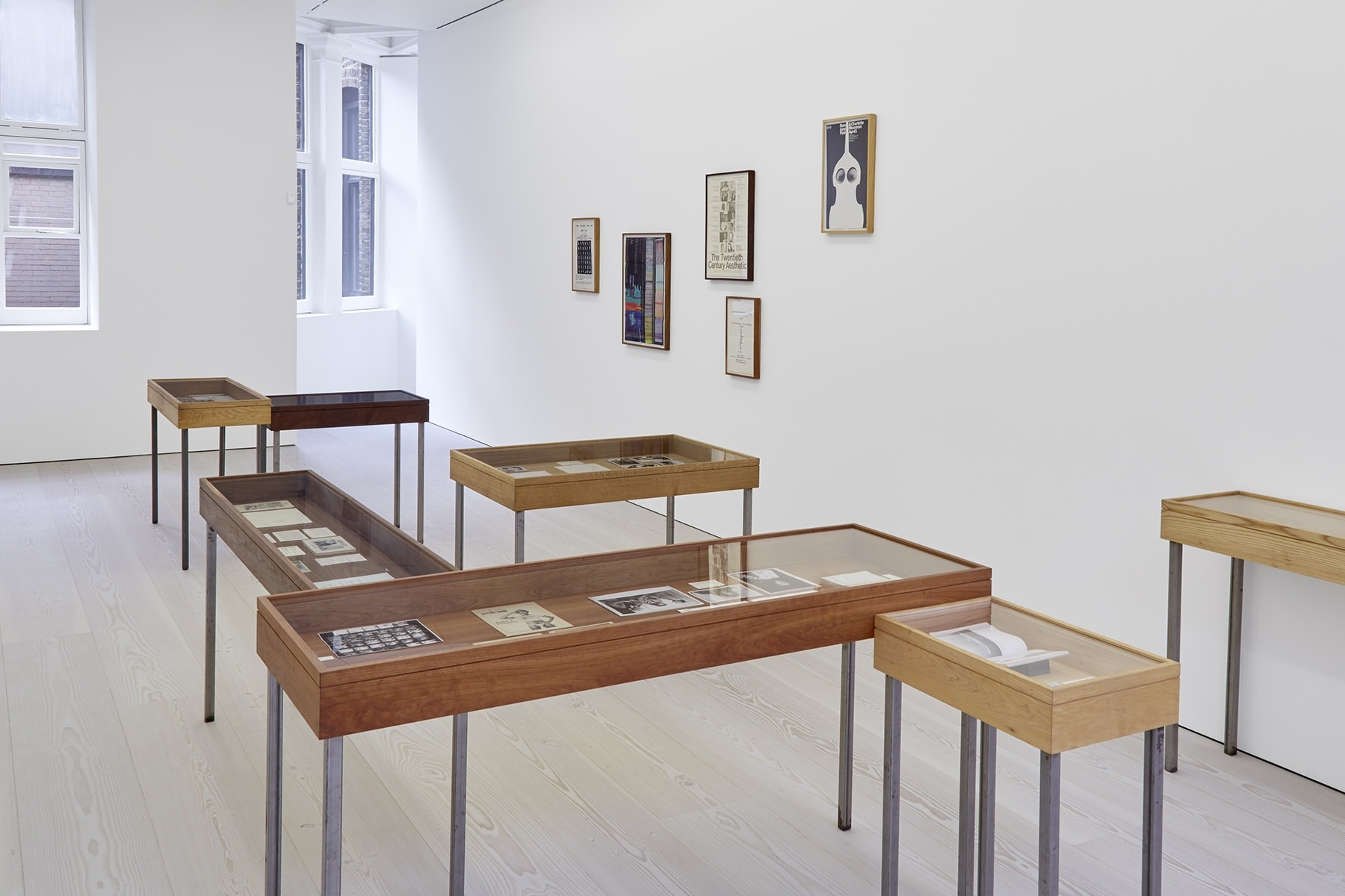 In a white space with light wood floors, several tables with glass tops act as display cases for various drawn works. Both colorful and black and white paintings and prints hang from the walls.