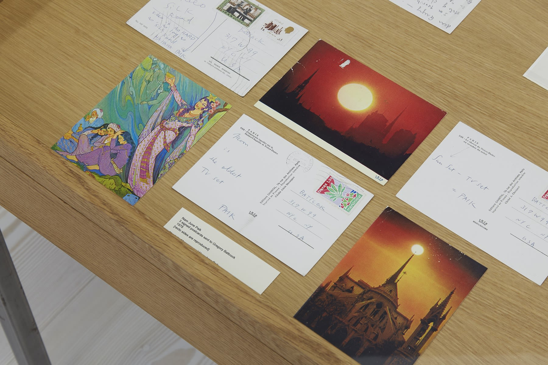 Several postcards, with writing, drawings, and images of sunsets, lie in a display case.