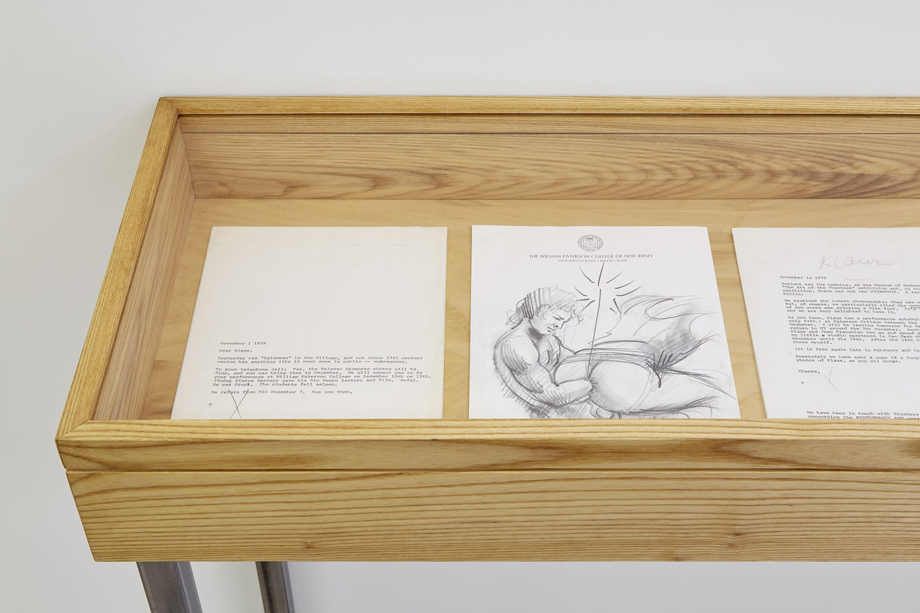 In a wooden display case, a couple of letters from 1979 to a man named Klaus, and a drawing on letterhead reading: THE WILLIAM PATTERSON COLLEGE OF NEW JERSEY.