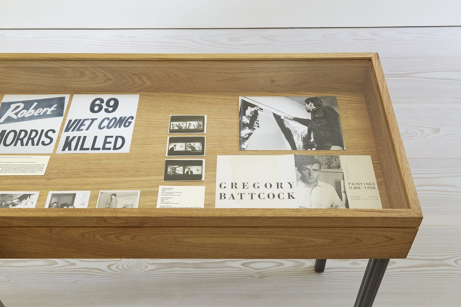 In a display case, various ads and newspaper headlines lie (Robert Morris, 69 VIET CONG KILLED), along with photos of painter Gregory Battcock, and a flier for an opening of his.