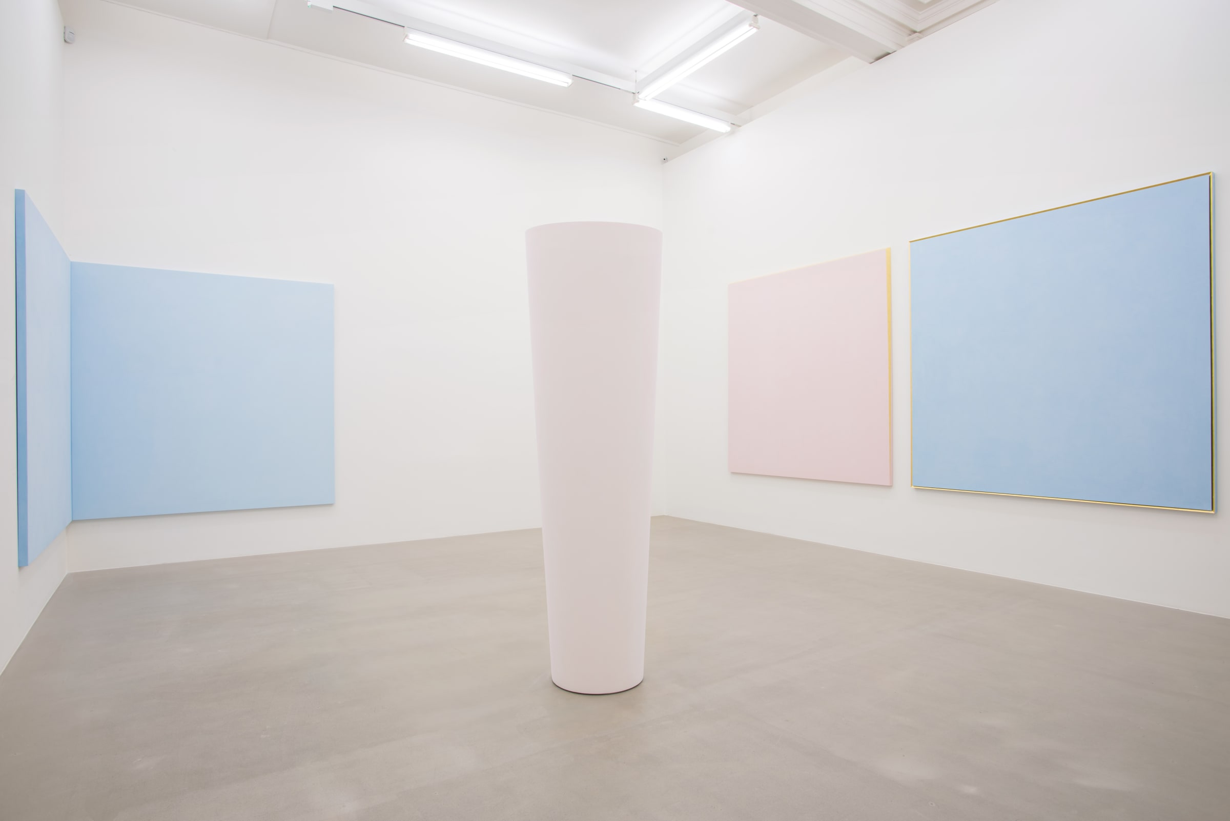 In a white room with grey stone floors, a light pink beam sits. On the right wall, a light pink painting hangs next to a sky blue painting, both framed by gold. In the left corner of the room, a light blue painting is bisected, sitting in equal halves on