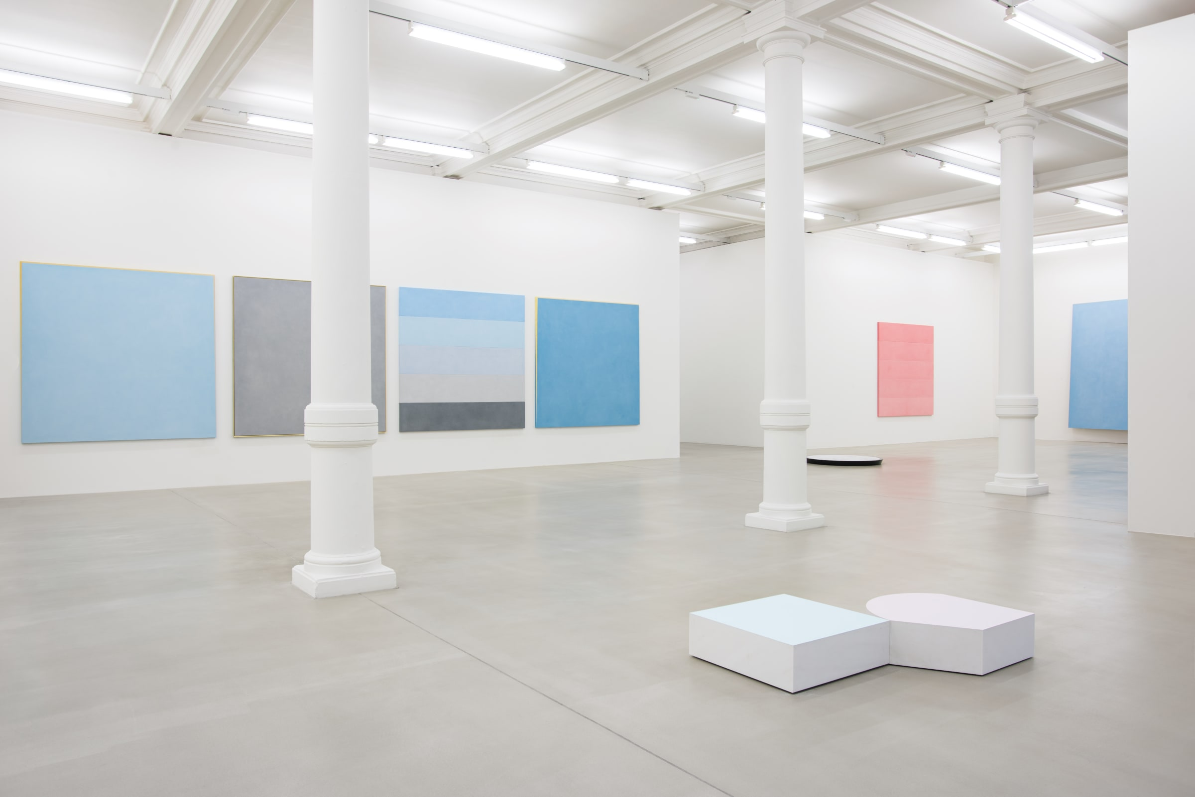 Various paintings of light shades (blue, grey, pink) line the walls of an all white space, with short white sculptures on the floor.