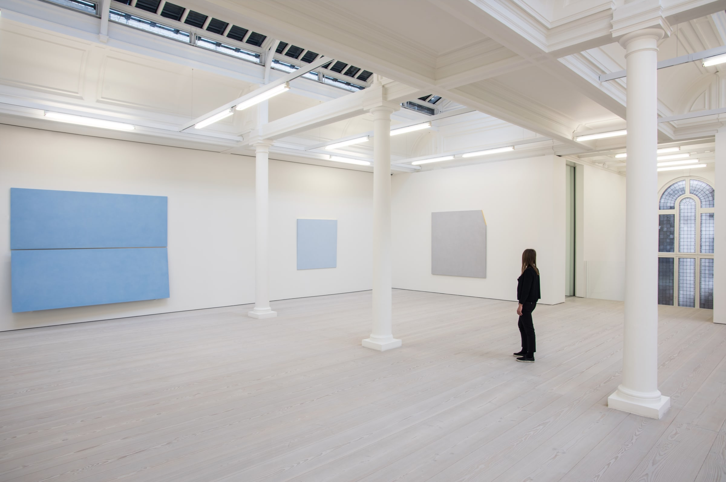In a large white space with columns, two large light blue paintings hang, with one light grey painting. A woman dressed in black looks at the art.