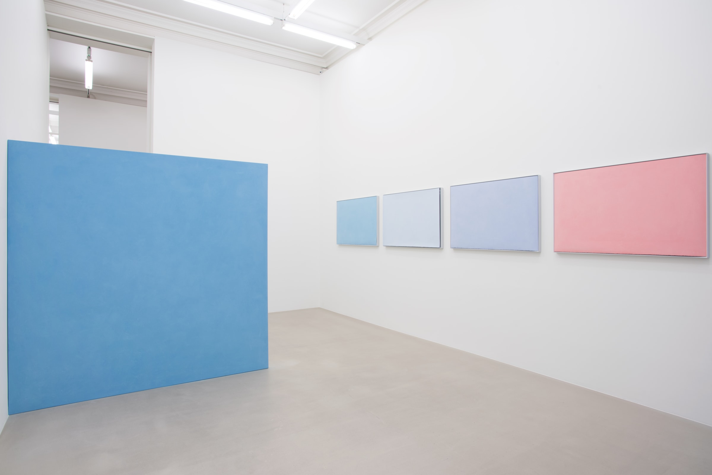 4 pastel colored paintings hang horizontally on the wall on the right. A large, light blue floating wall comes out perpendicularly from the wall on the left.