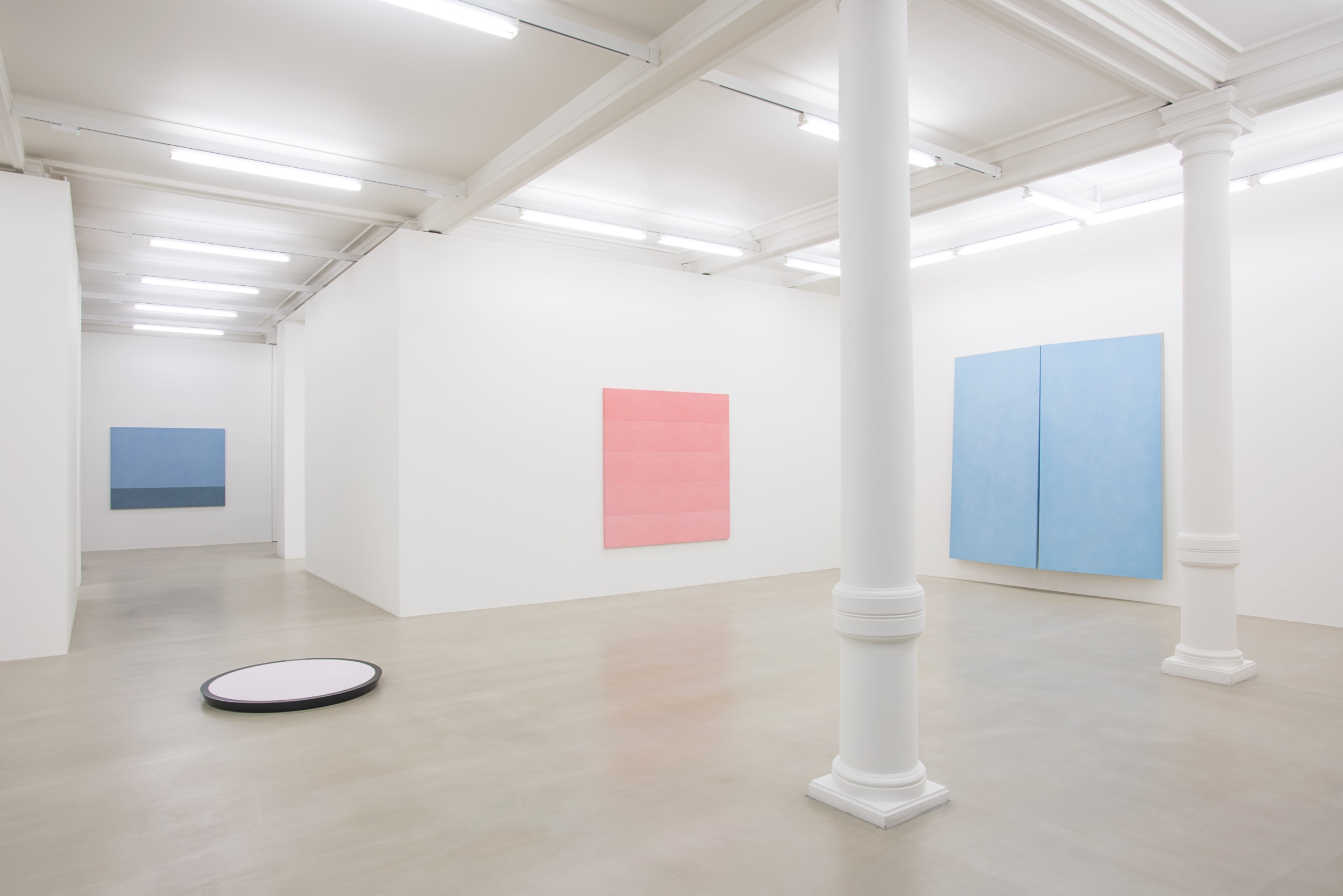 3 pastel paintings hang on the wall around a corner. There are 2 white columns in the room and a circular white object on the floor.