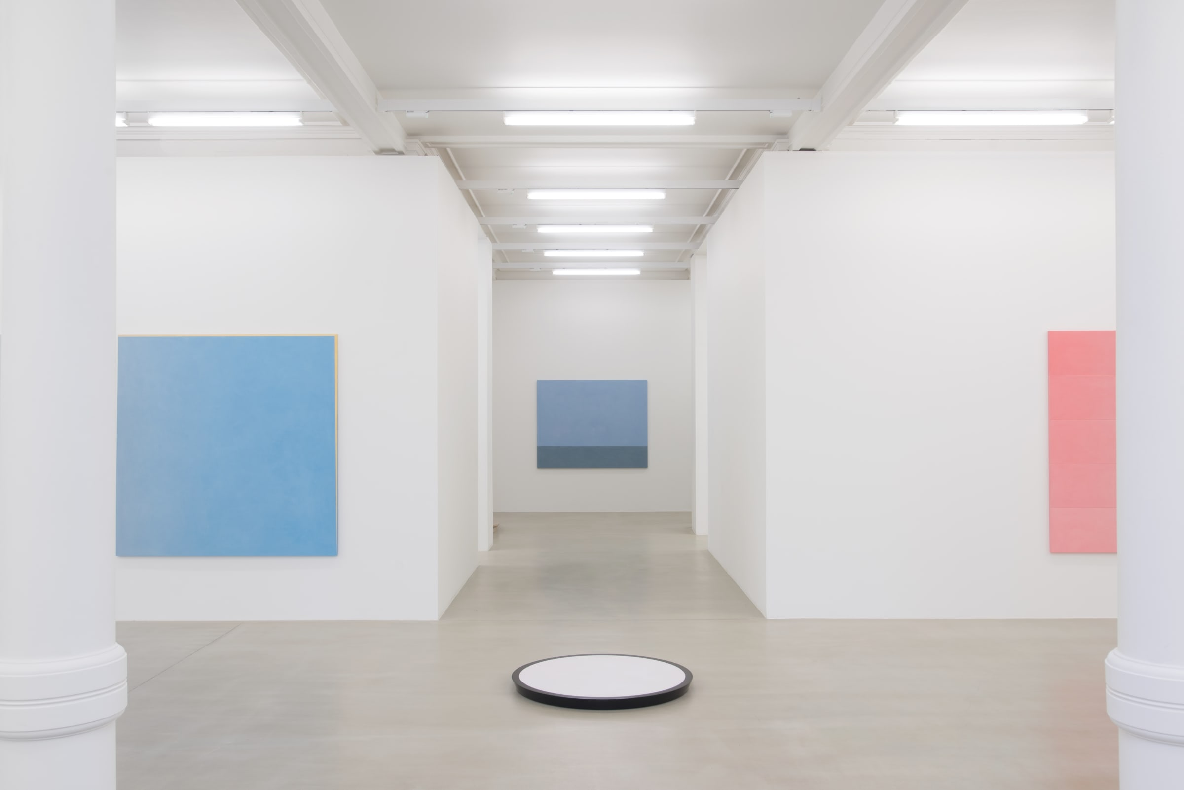 2 paintings hang on either side of a hallway, one pink and one blue. There is a blue painting at the end of the hall and a white circular object in the center.