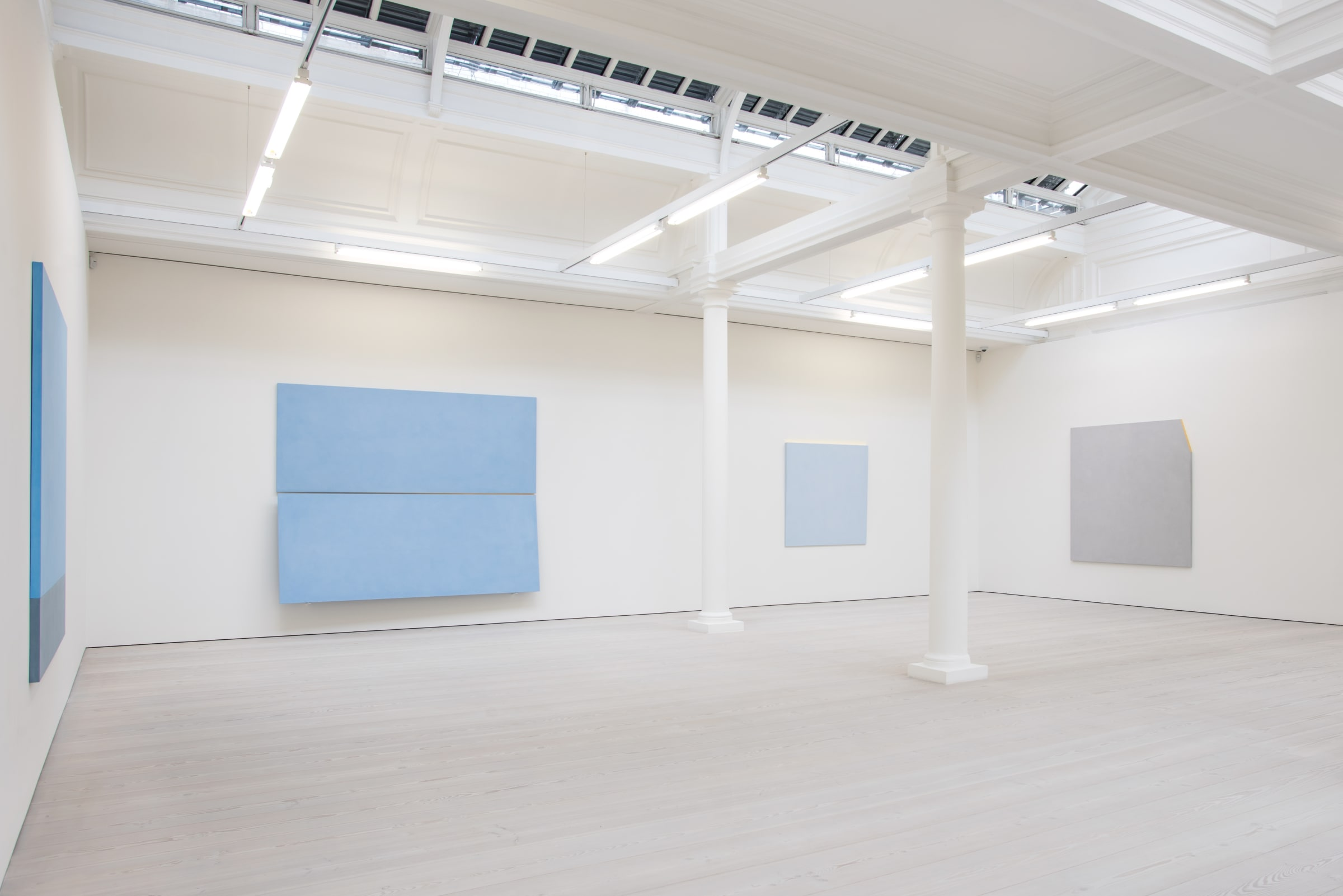 4 blue and gray paintings hang in a large white room. There is a long skylight in the ceiling and 2 white columns.