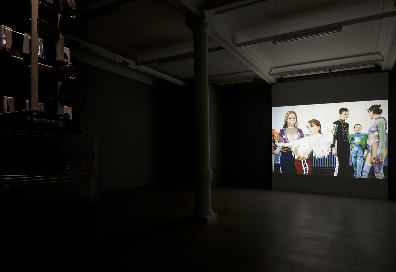 A projection in a darkened room shows 5 figures in carnival costumes. The projector is visible on the left.