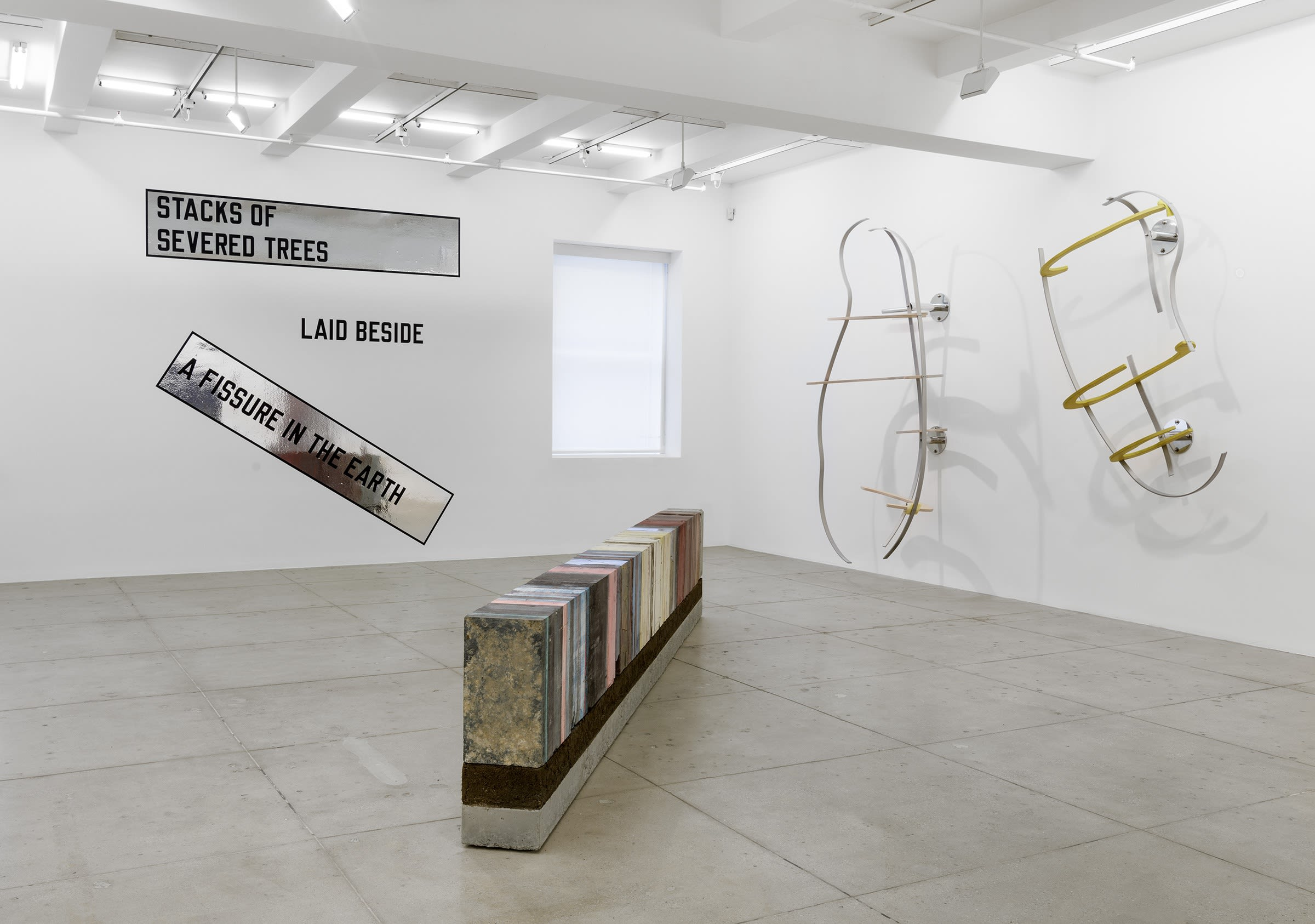 Various artworks are arranged in the corner of a white room with a window; text on a reflective banner, metal armatures painted white and yellow, and a long, rectangular multi-colored sculpture.