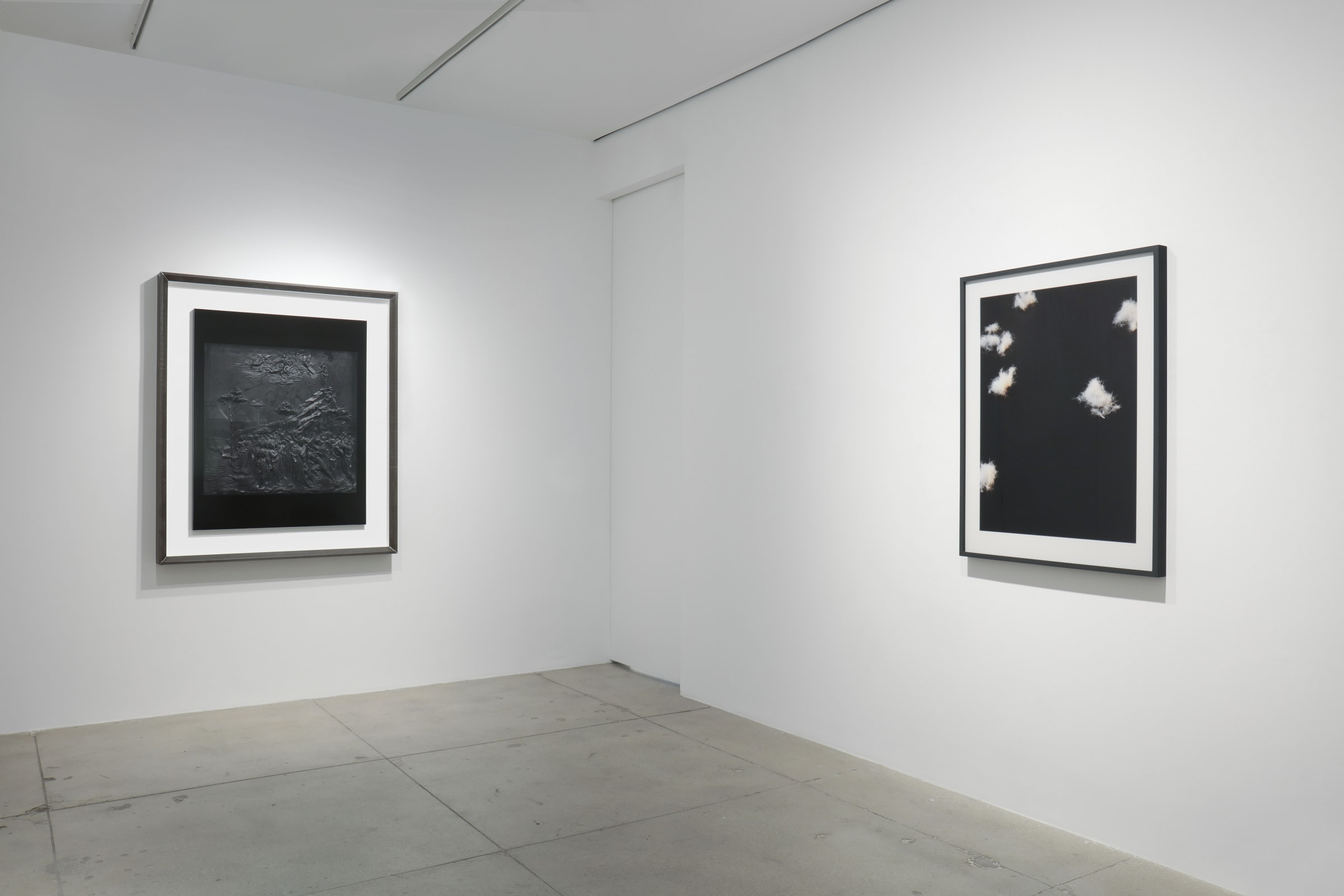 2 framed artworks hang in the corner of a white room. On the left appears to be an embossed landscape, while on the right is a black and white photograph of clouds.