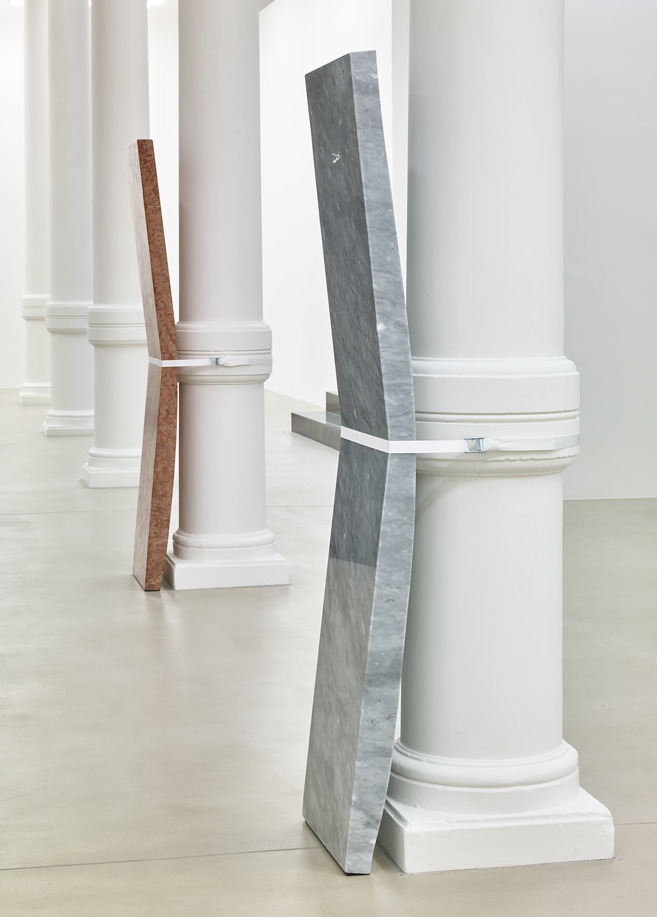 Installation view, slabs of stone strapped to pillars in a row.