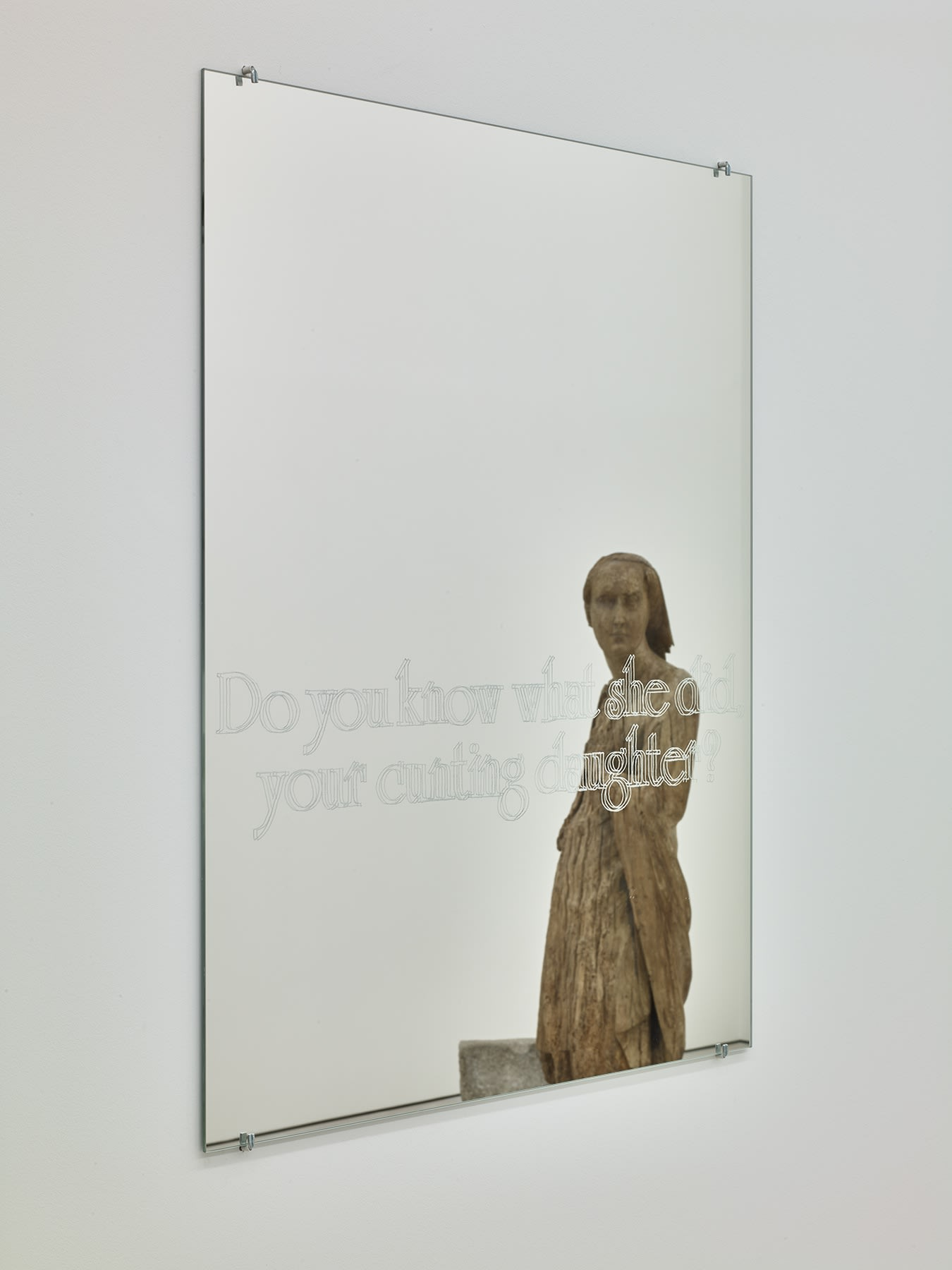 Image of mirror with translucent words reflecting a figurative statue facing the mirror.