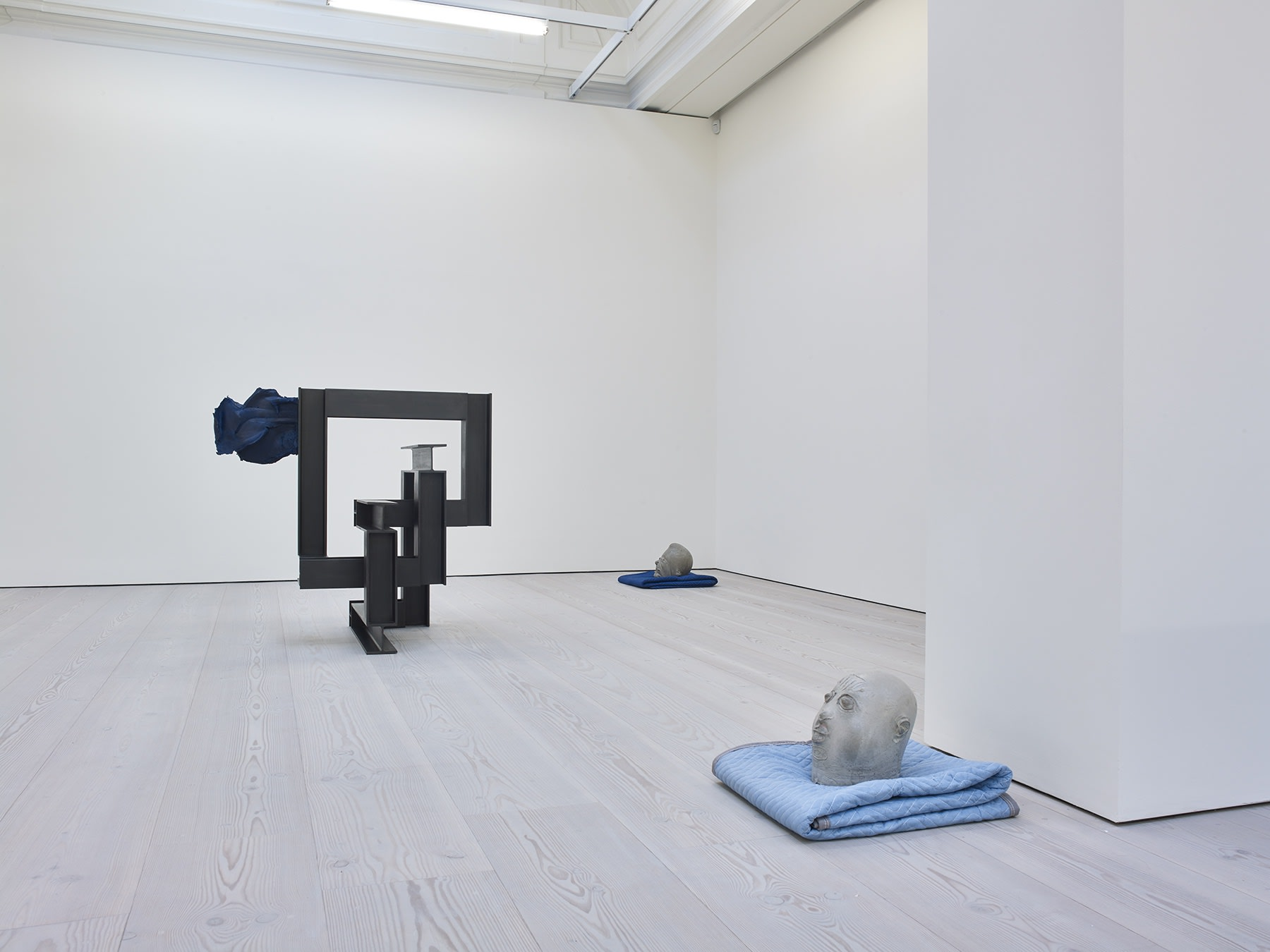 Gallery view, two abstract clay heads rest on blue blankets. To the left there is a geometric black square sculpture.