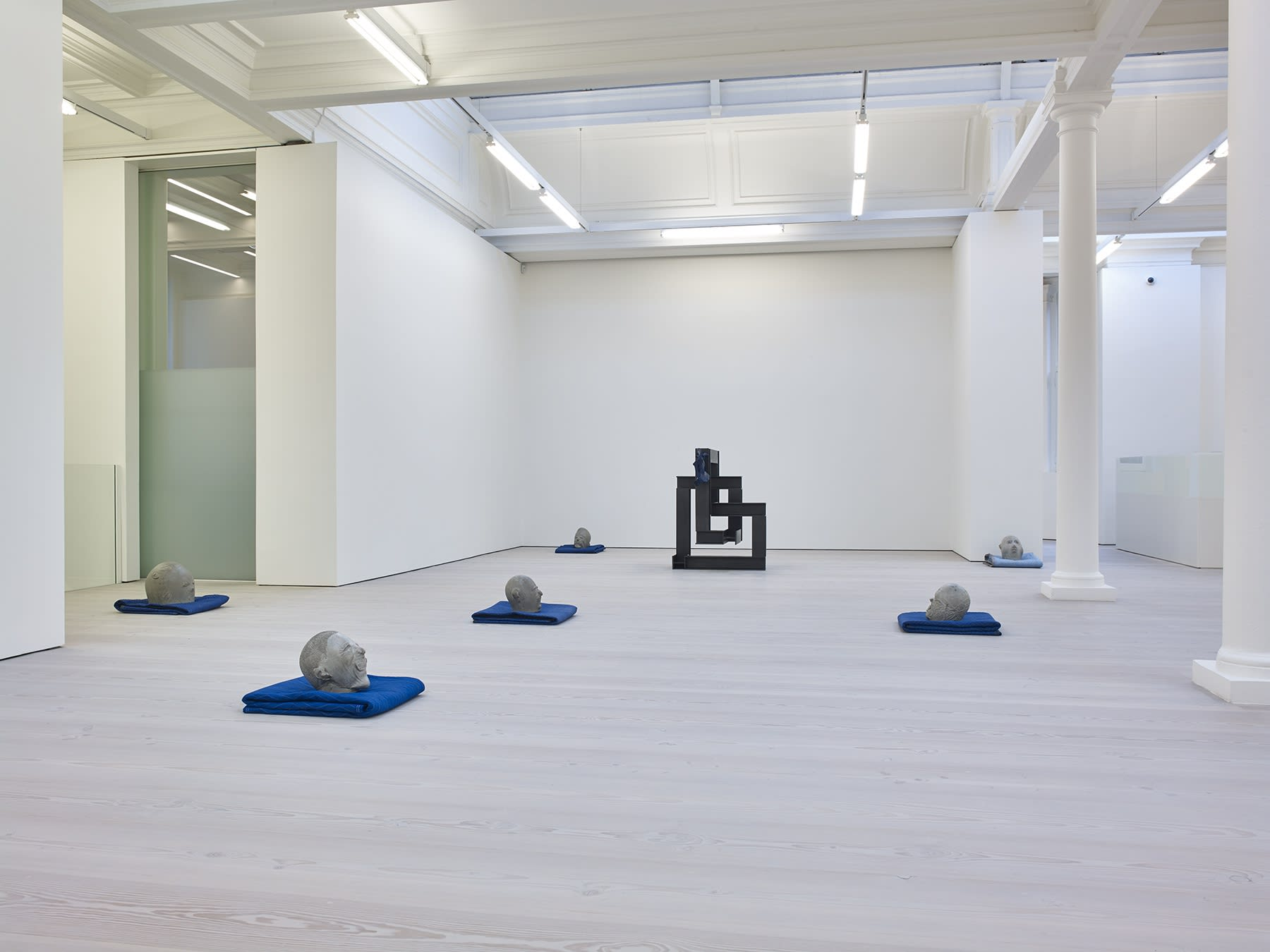 Gallery view, abstract clay heads rest on blue blankets, there is one geometric black square sculpture.
