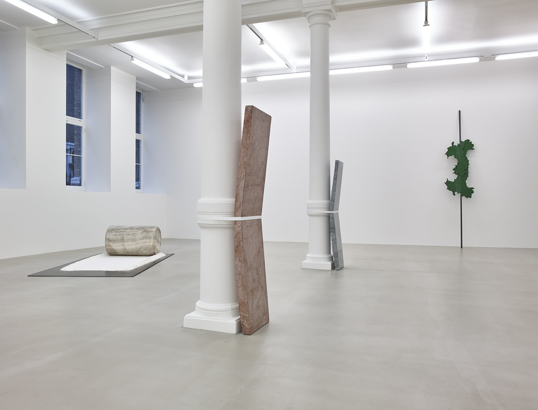 Installation view, slabs of stone strapped to pillars in a row and a cylinder stone on pallet.