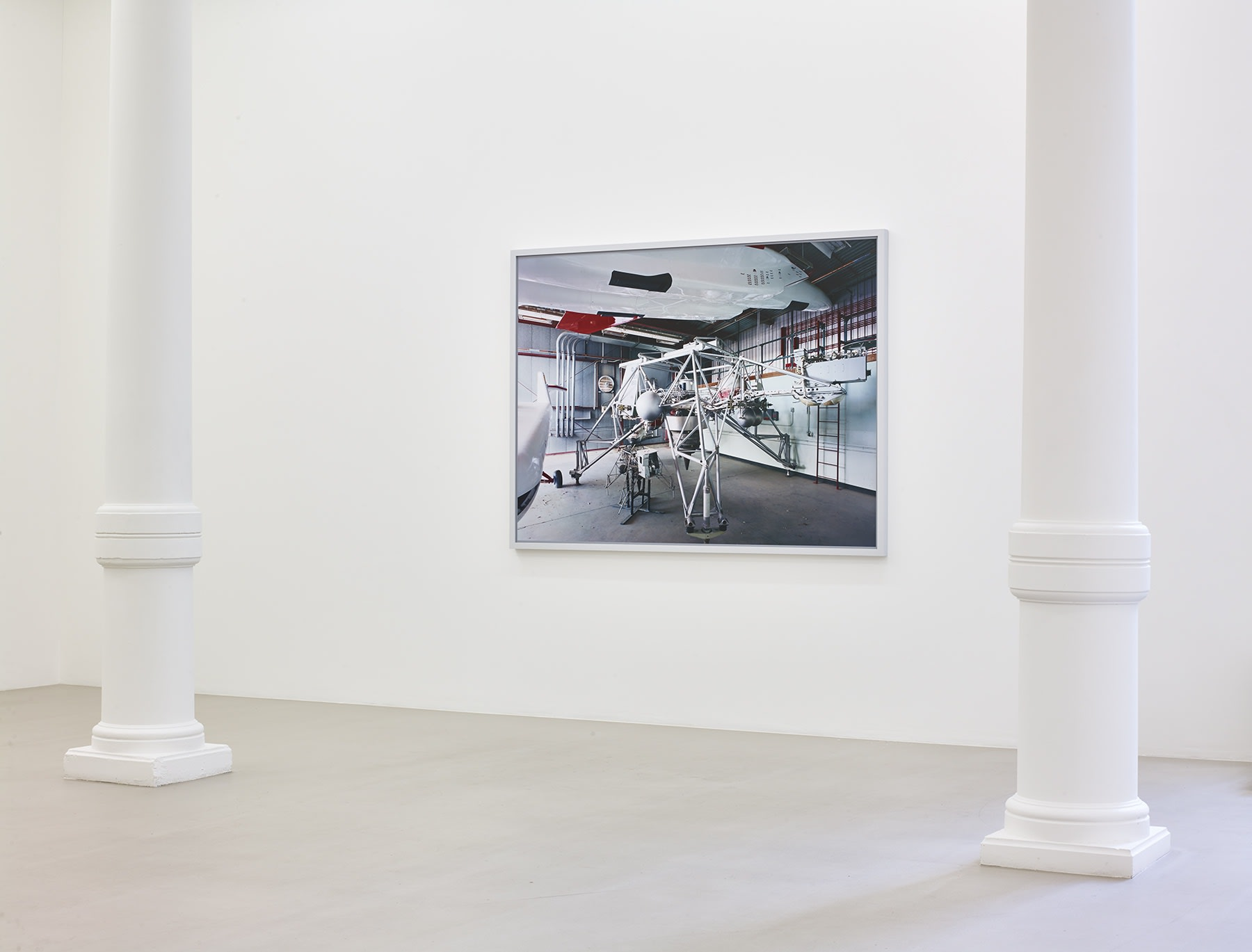 In a white gallery space,  a photograph of an unidentified piece of machinery hangs on a white wall.