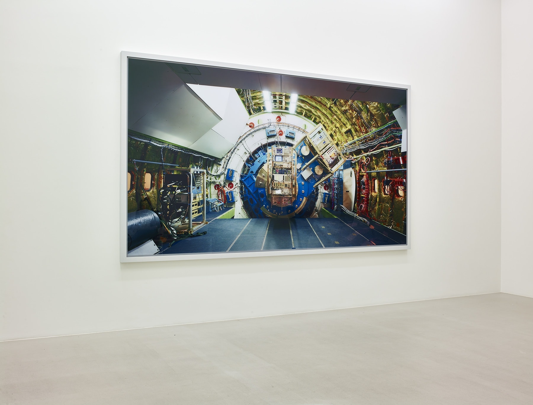 On a white wall, a large rectangular photo, framed in white, shows the interior of what appears to be a spaceship - heavy gold, blue, and white machinery.