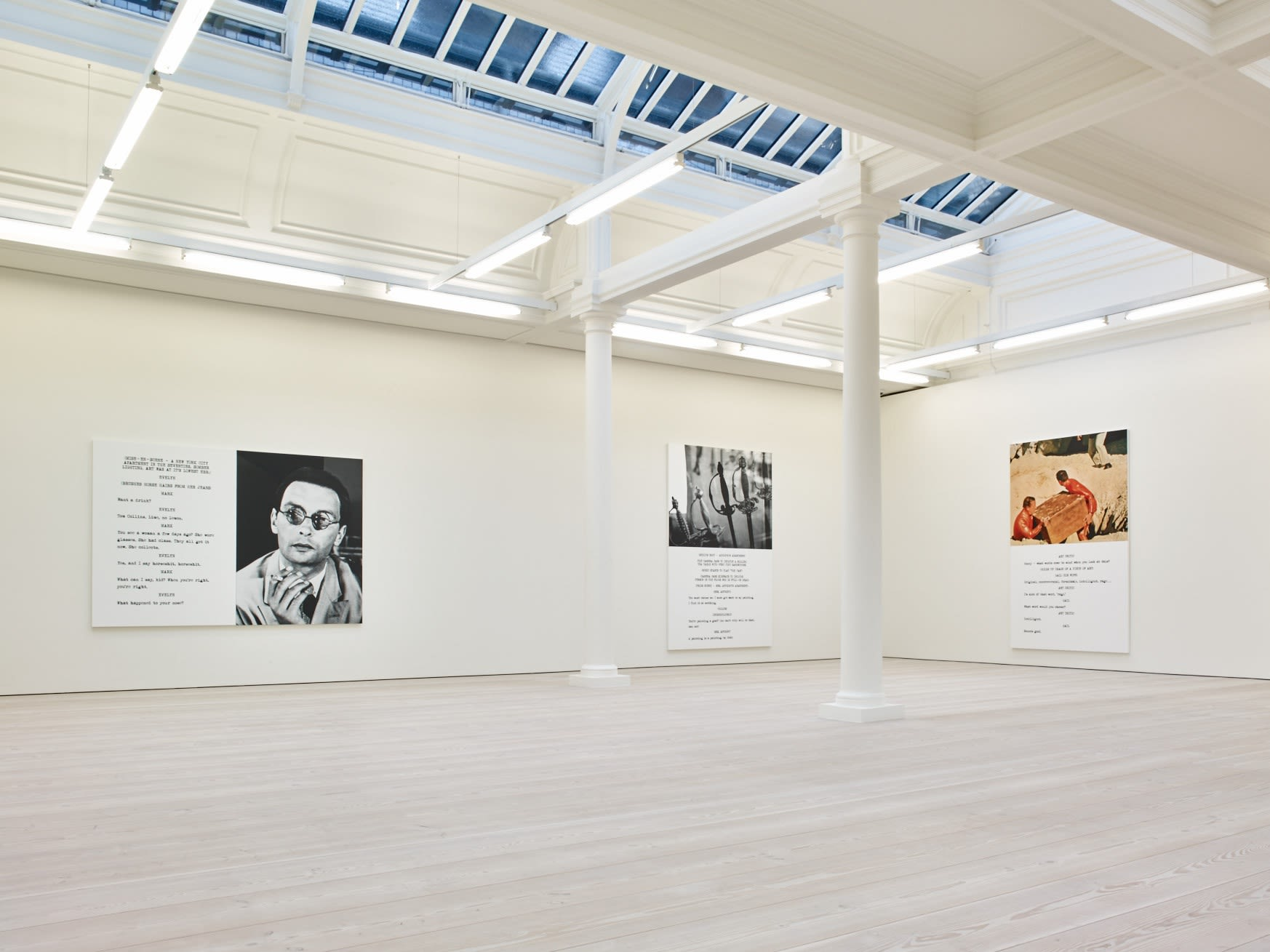 In a large white space with columns and a long skylight, 3 large paintings hang. Each are roughly half image and half text, which is in the format of a film script.