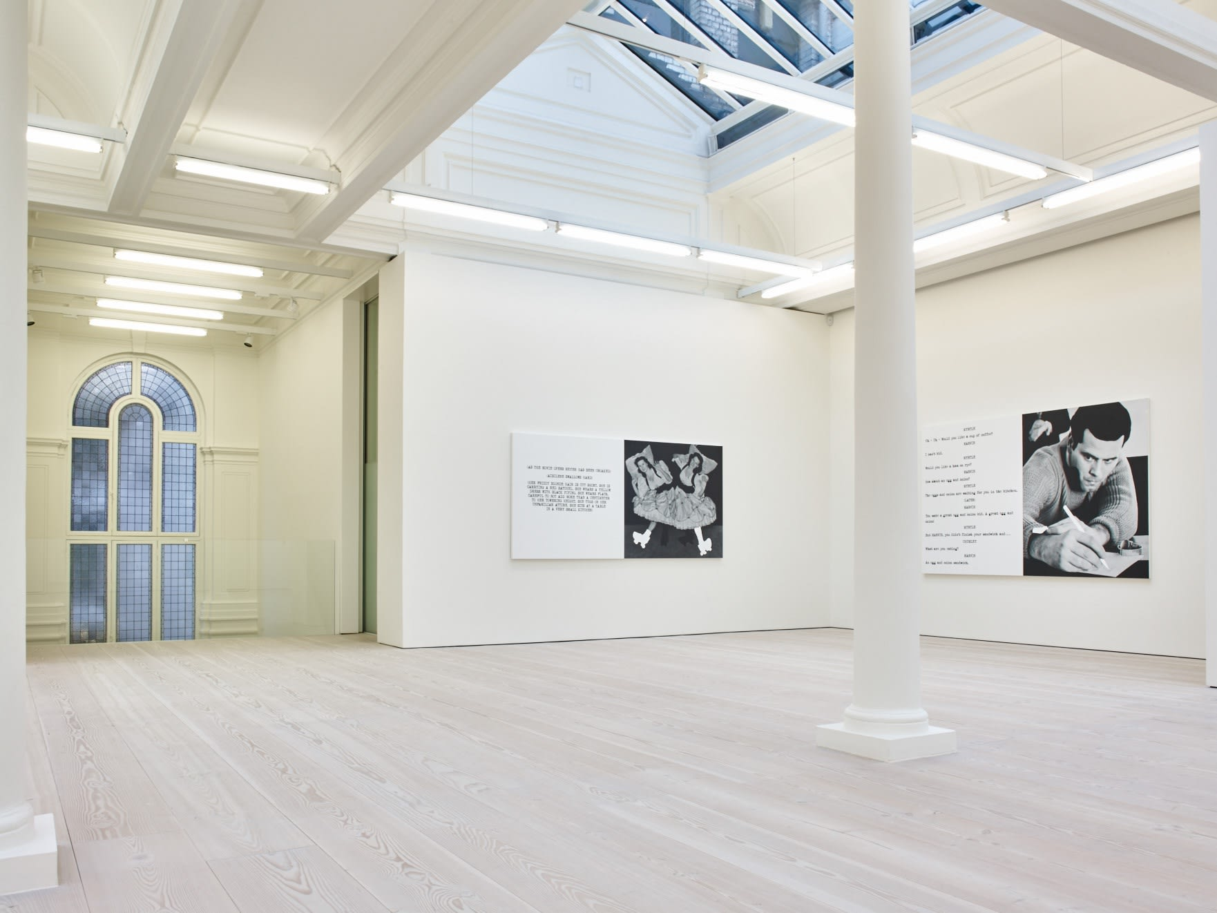 In a large white space with columns, a window, and a long skylight, 2 large paintings hang. Each are roughly half image and half text, which is in the format of a film script.