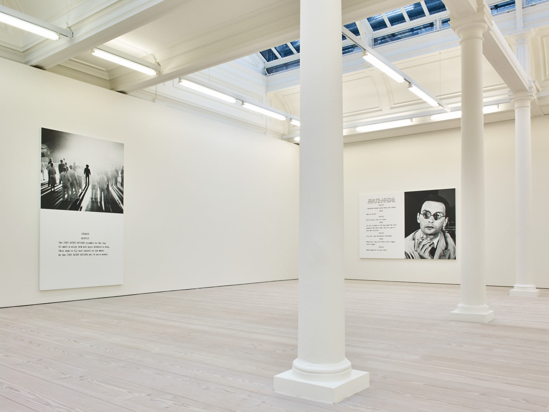 In a large white space with columns and a long skylight, 2 large paintings hang. Each are roughly half image and half text, which is in the format of a film script.