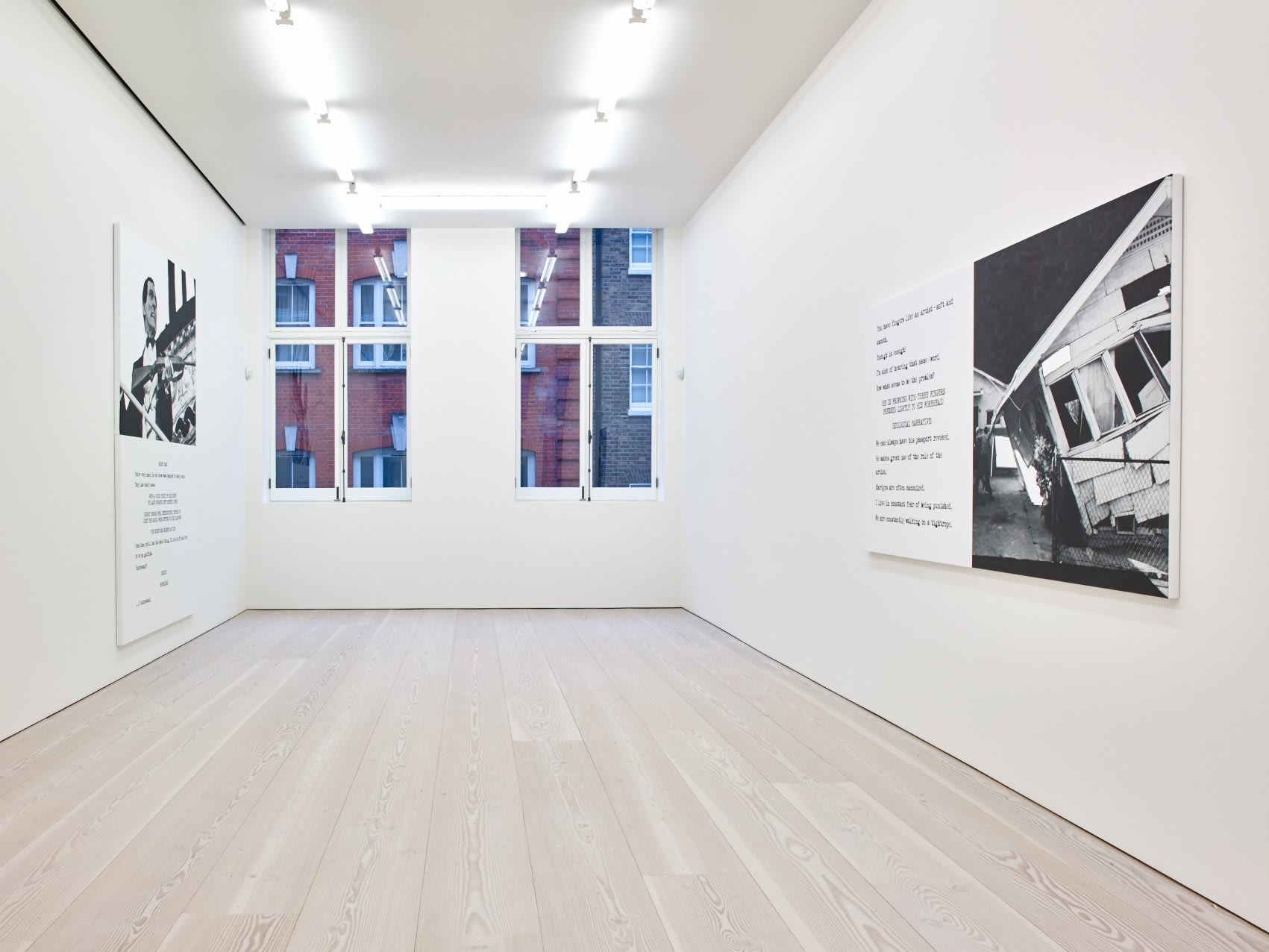 In a large white space with two large windows in the middle, 2 large paintings hang on opposite walls. Each are roughly half image and half text, which is in the format of a film script.