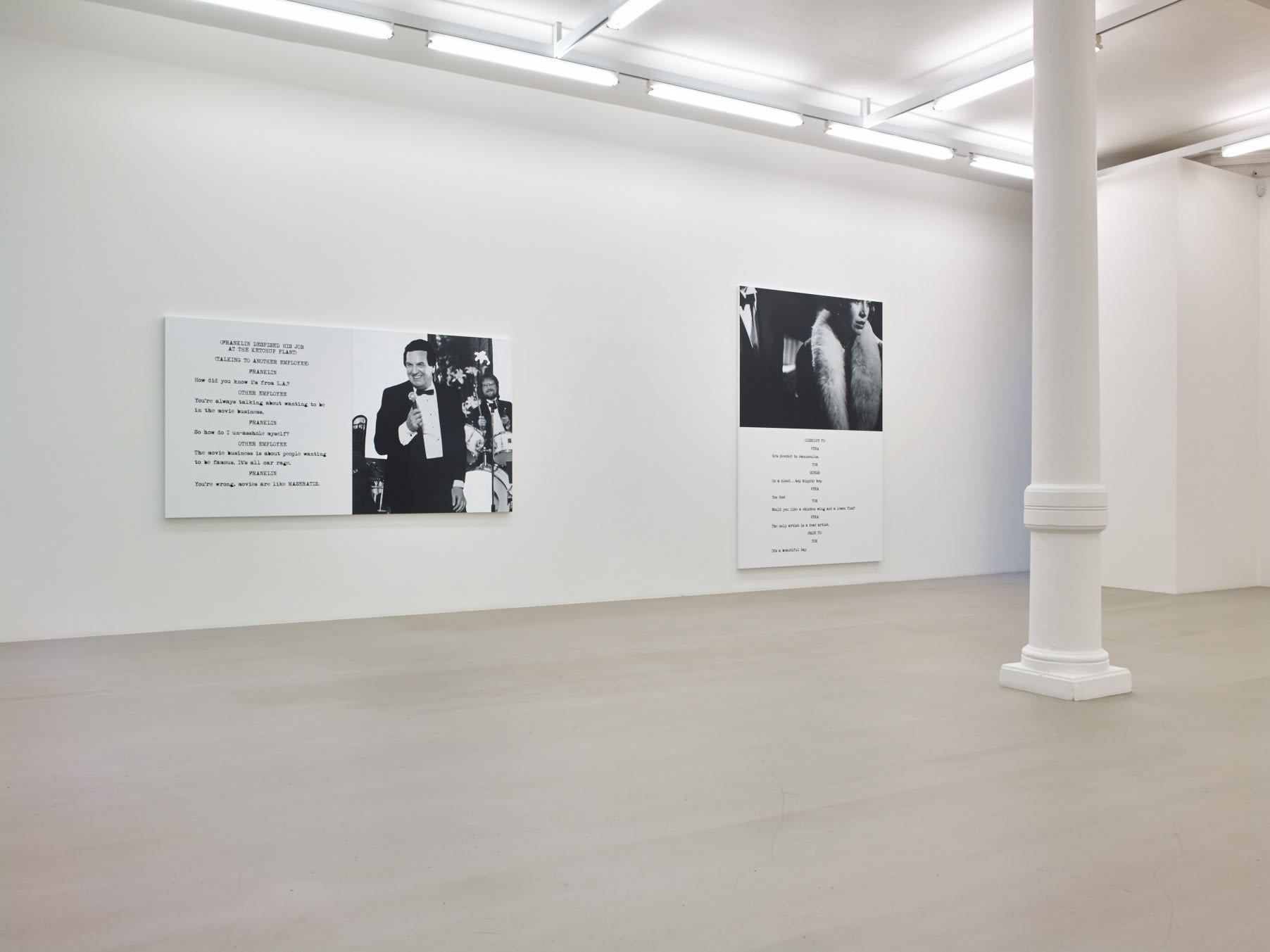 In a large white space with columns, 2 large paintings hang. Each are roughly half image and half text, which is in the format of a film script.