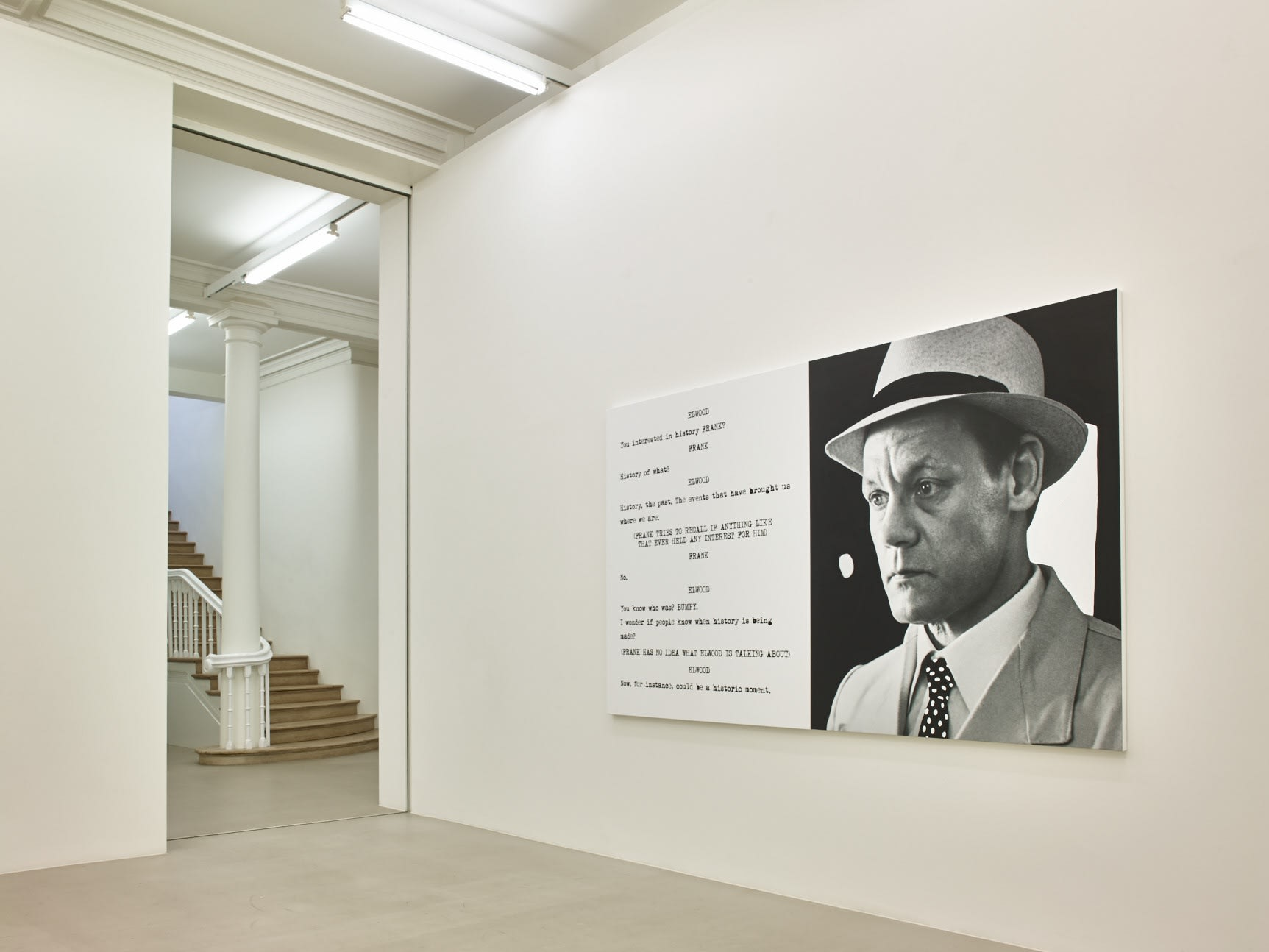 In a large white space with columns, a large paintings hangs, roughly half image and half text, which is in the format of a film script. The image is of a man in a suit and fedora. To its left, in the background, a stone staircase leads upstairs.