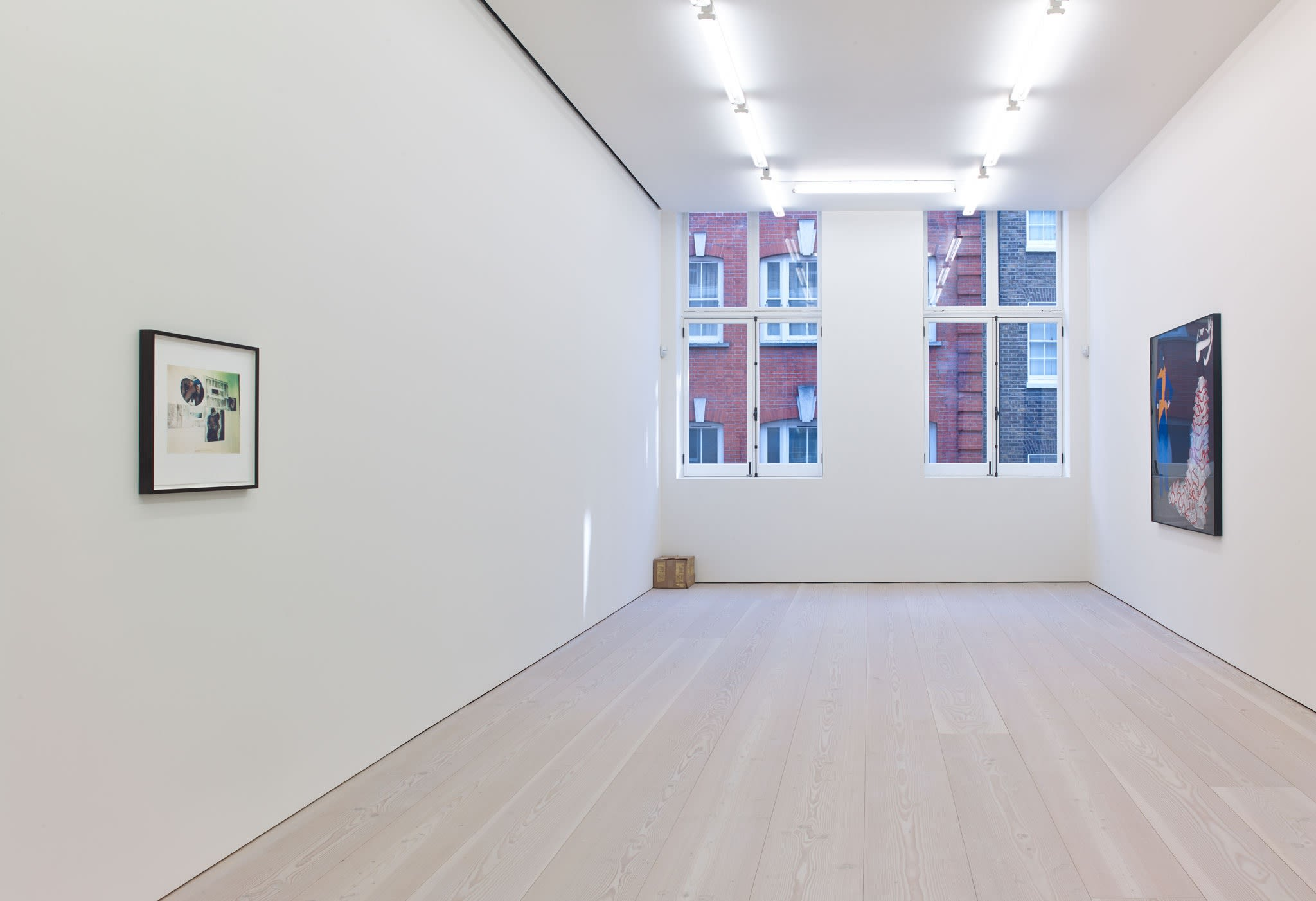 In a white room with windows straight ahead, a small print hangs on the left wall, a large colorful work on the right wall, and a small cardboard box sits in the left corner under the window.