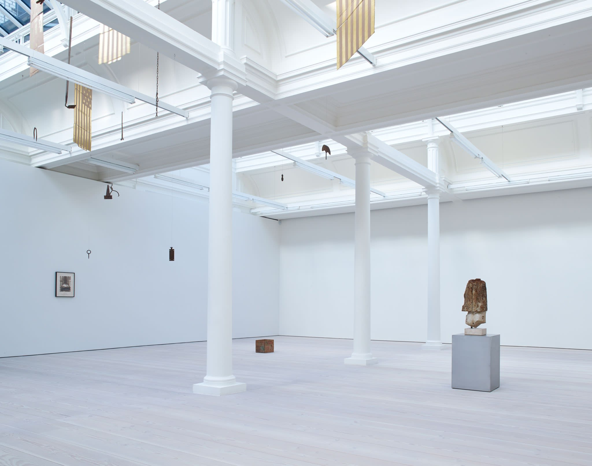 In a large white space with a long glass skylight, sculptures hang from the ceiling - most seem to be American flags, with 13 stars, made out of gold painted cardboard. A small cardboard box sits on the floor as well.
