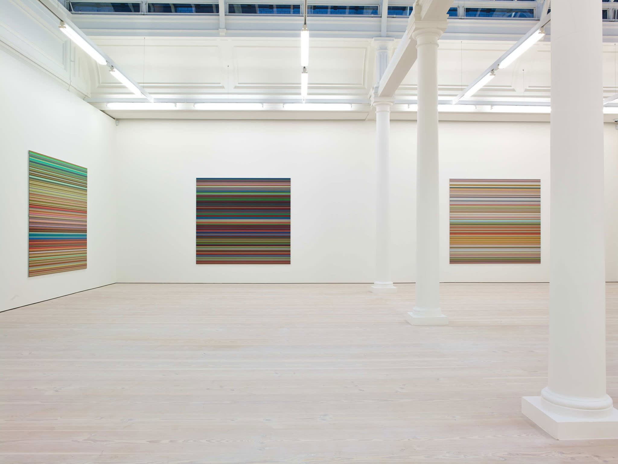 In a large white space with columns and skylights, three paintings hang, all square and about 6 by 6 feet. They are all made up of hundreds of perfect horizontal strips of various colors.