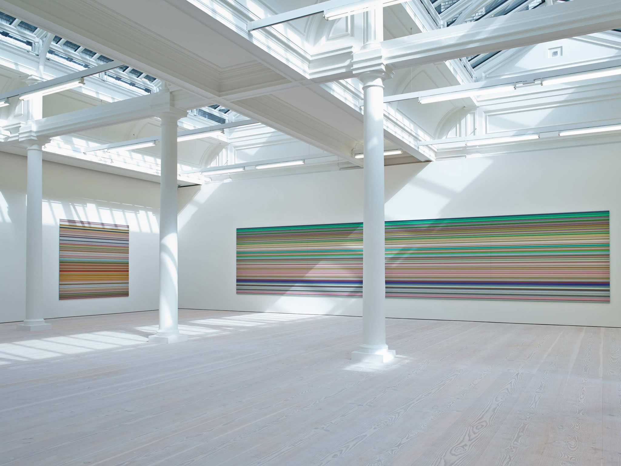In a large white space with columns and skylights, an enormous painting hangs, light from the skylight shining on it. It is made up of hundreds of perfect horizontal strips of various colors, mostly light green in hue, with a great deal of reds and blues.