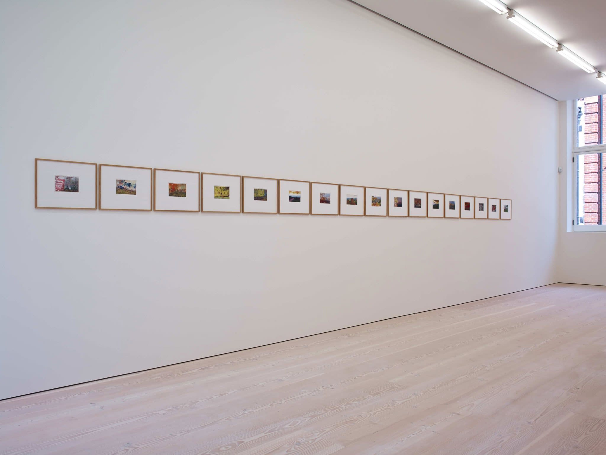 On a long white wall, about 15 paintings hang, all very small, and bordered by large white frames, further bordered by wood. The paintings are all done over prints of film photographs.