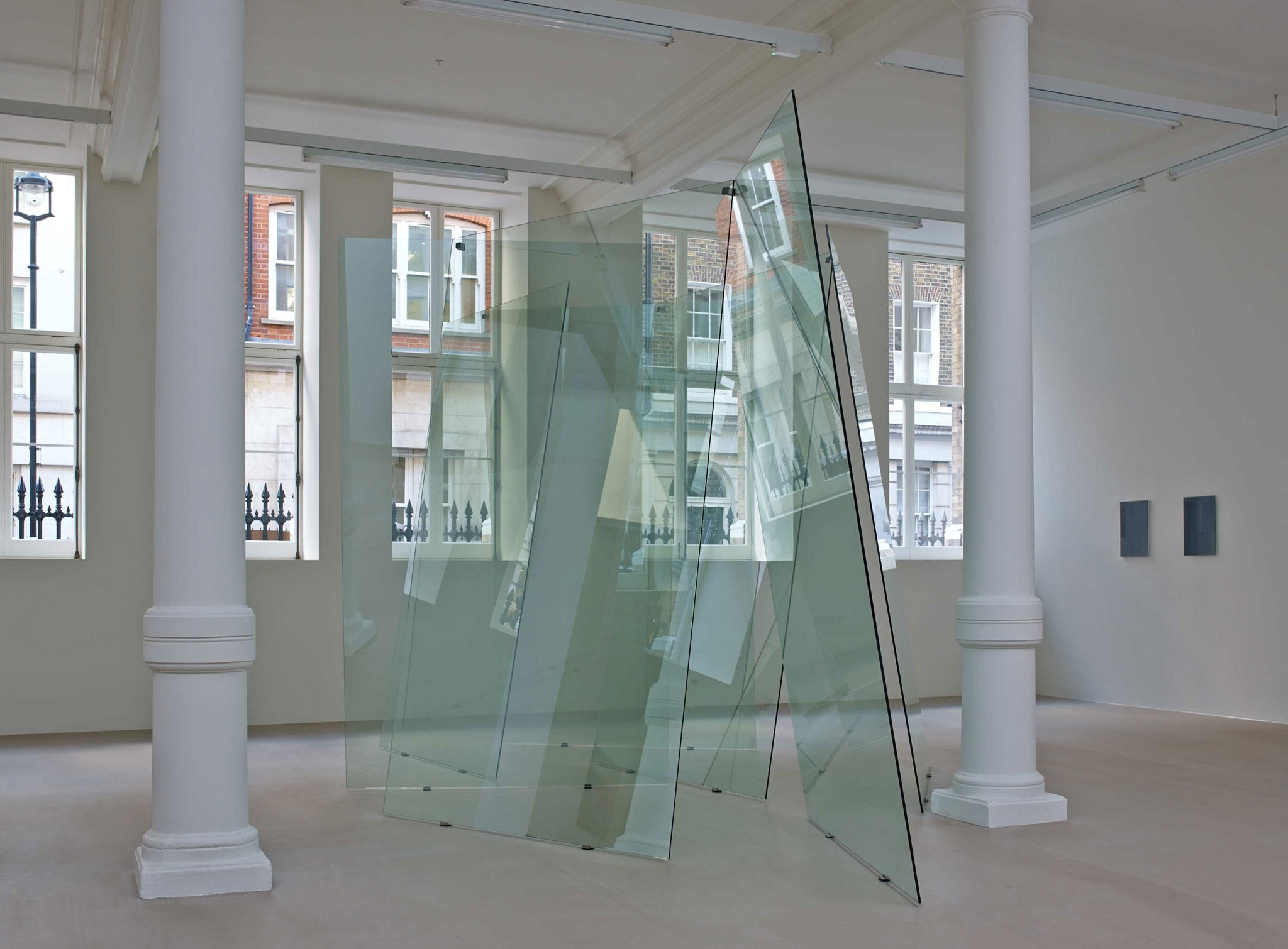 In a large white space with columns and many windows, several glass planes lean on each other unevenly, making a large sculpture.