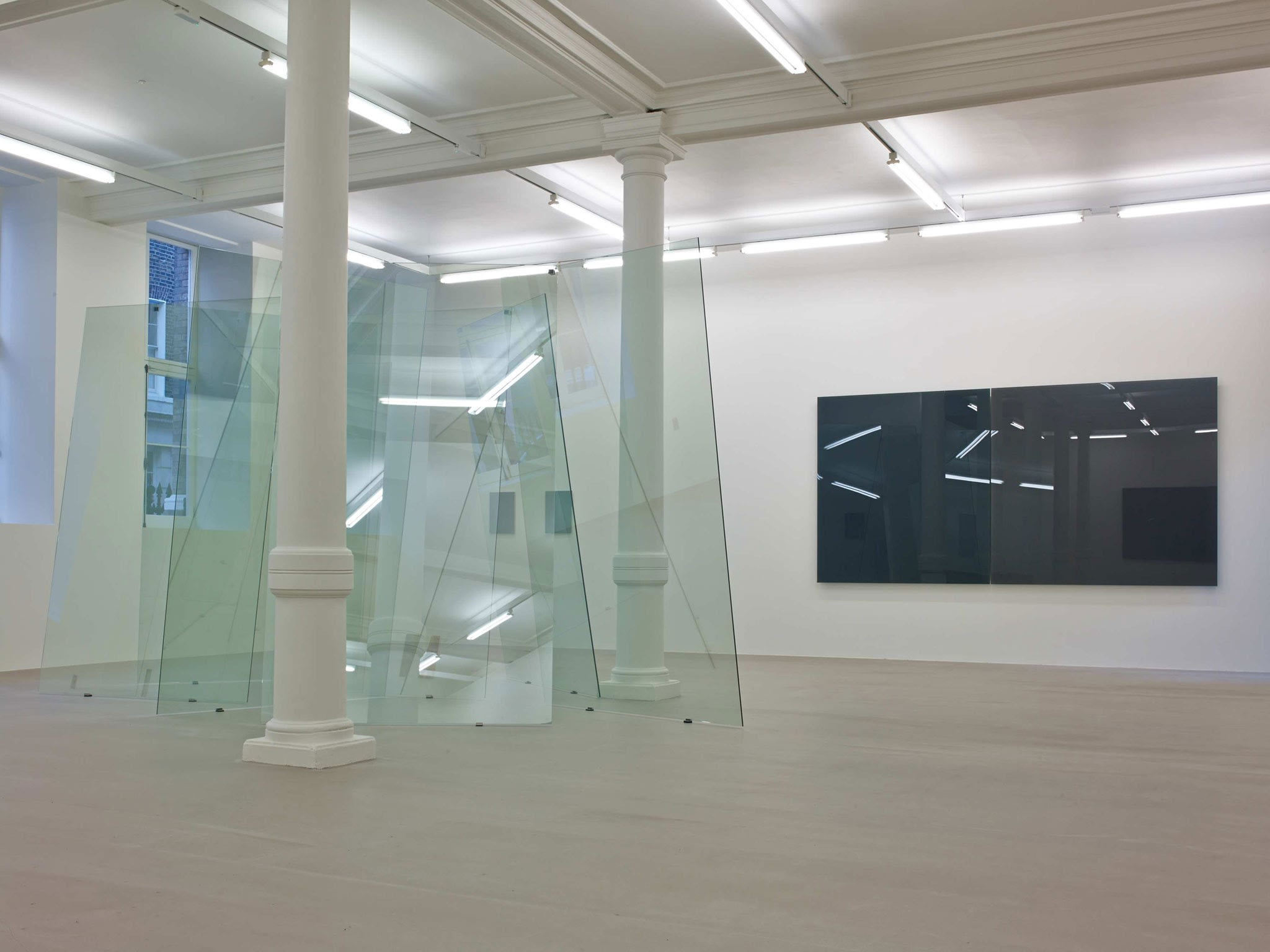 In a large white space with columns and many windows, several glass planes lean on each other unevenly, making a large sculpture. Behind it on a wall, two large square glass panes hang, one black and one grey.