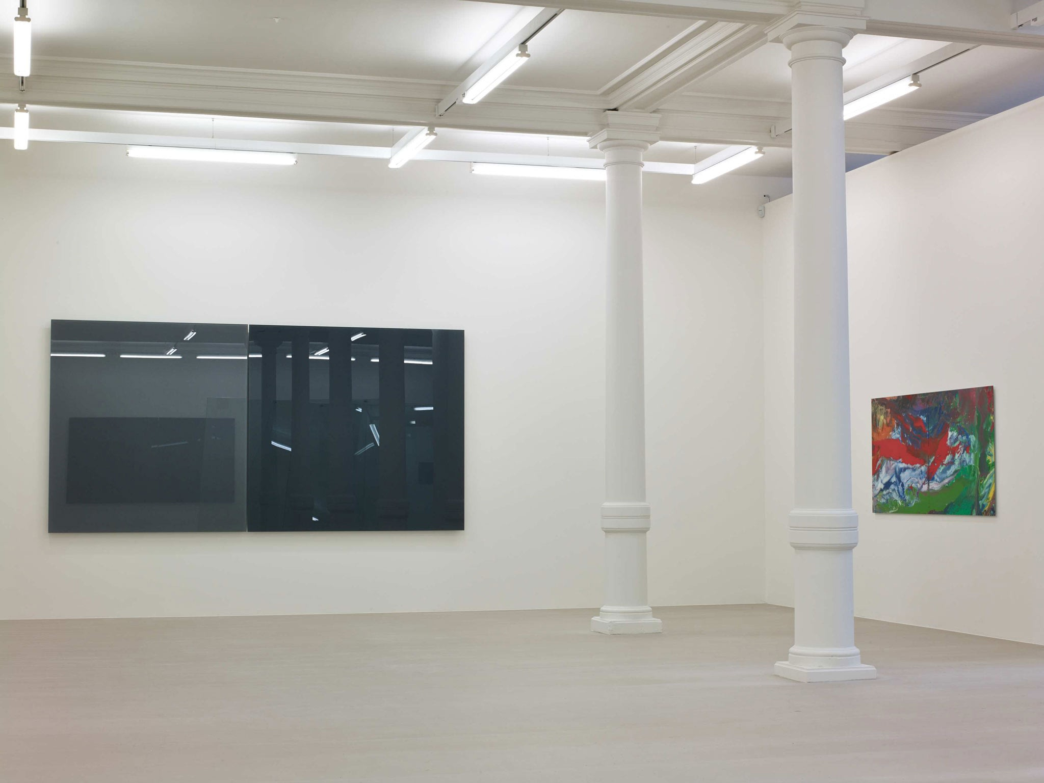 In a large white space with columns, two large square glass panes hang next to each other on a wall, one black and one grey. On the wall to their right is a small abstract painting, of reds, whites, and greens.