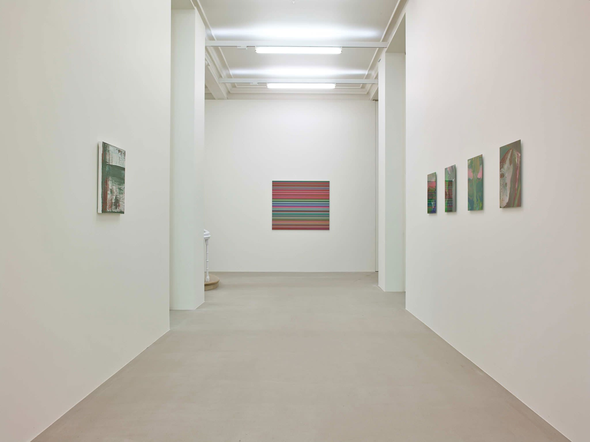 On a white wall down a hallway is a square painting, made up of hundreds of perfect horizontal strips of various colors. On both walls of the hallway hang small abstract paintings (1 right, 4 left), mostly green in hue.