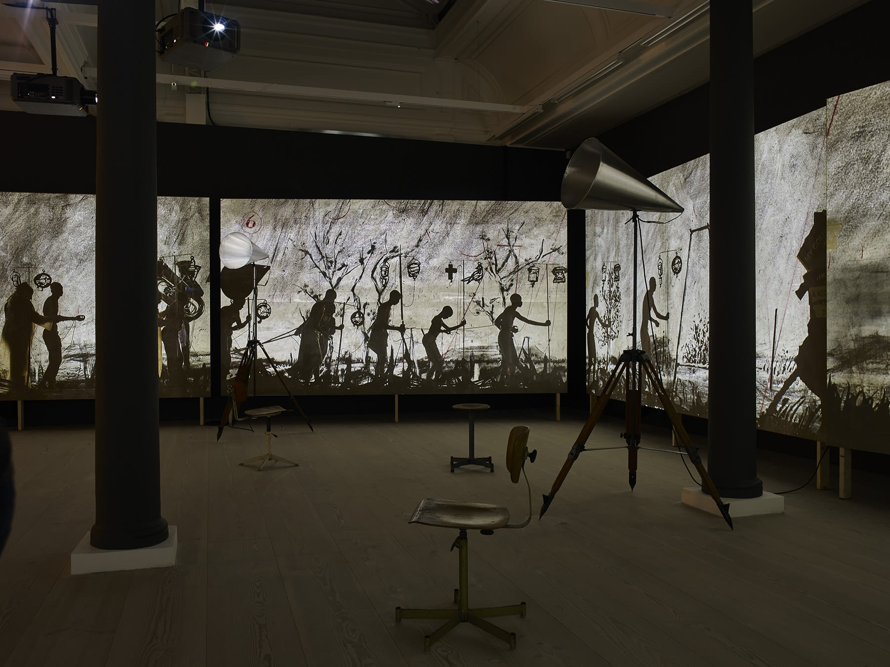 In a large dark space with columns, stools, and large objects resembling megaphones, several large video screens create a panoramic film, showing several characters, both people and sculptural representations of people's heads, walking through a marsh.