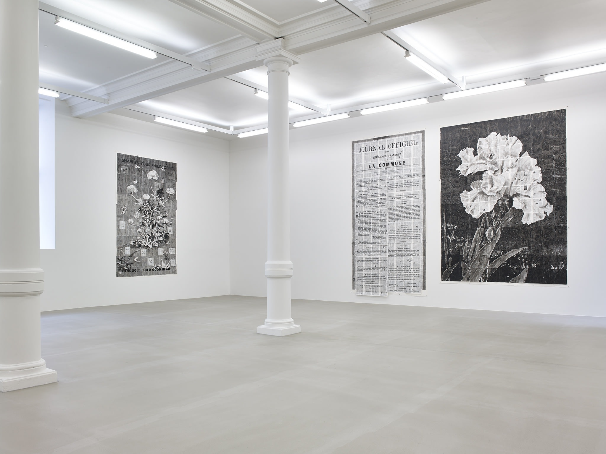 In a large white space with columns, three large black and white paintings hang, all made up of many small pieces of paper. On the left wall, a bush of flowers. On the right wall, a french newspaper (JOURNAL OFFICIEL), and a large Iris flower.