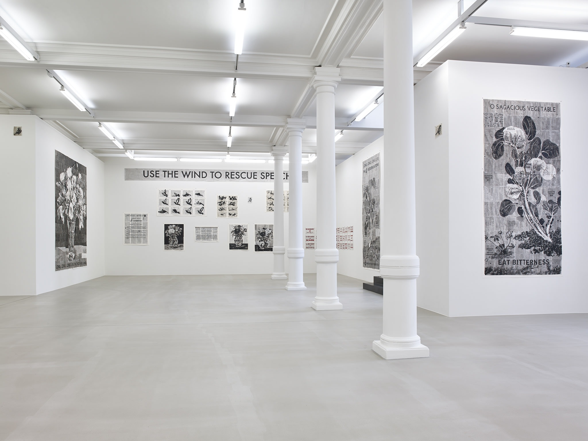 In a large white space with columns, many black and white paintings hang, of various sizes, all made up of smaller pieces of paper, except a large sign which hangs overhead, reading: USE THE WIND TO RESCUE SPEECH.